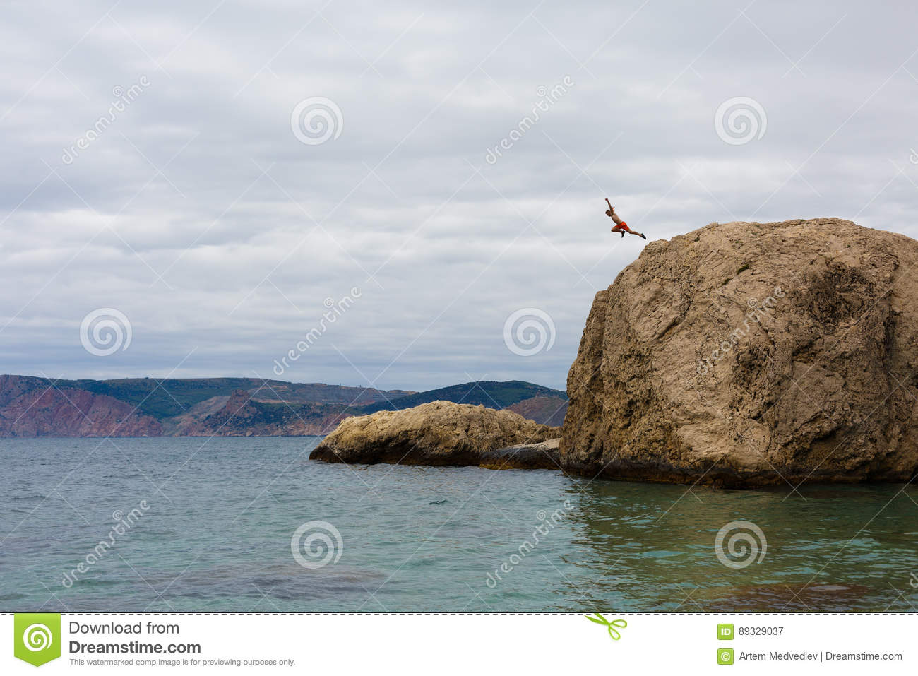 Brave Man Jumps From High Cliff Rock Into Water Of Sea
