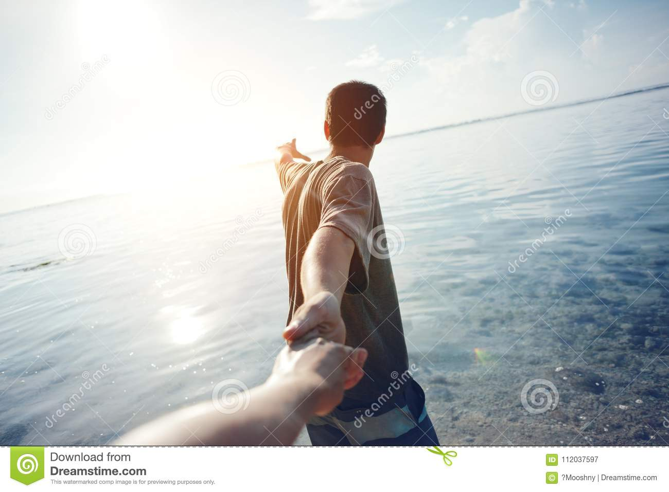Brave man guiding traveling woman through the water in ocean