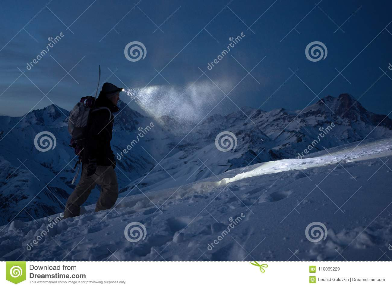 Brave night explorer climbs on high snowy mountains and lights the way with a headlamp. Extreme expedition. Ski tour. Snowboarder