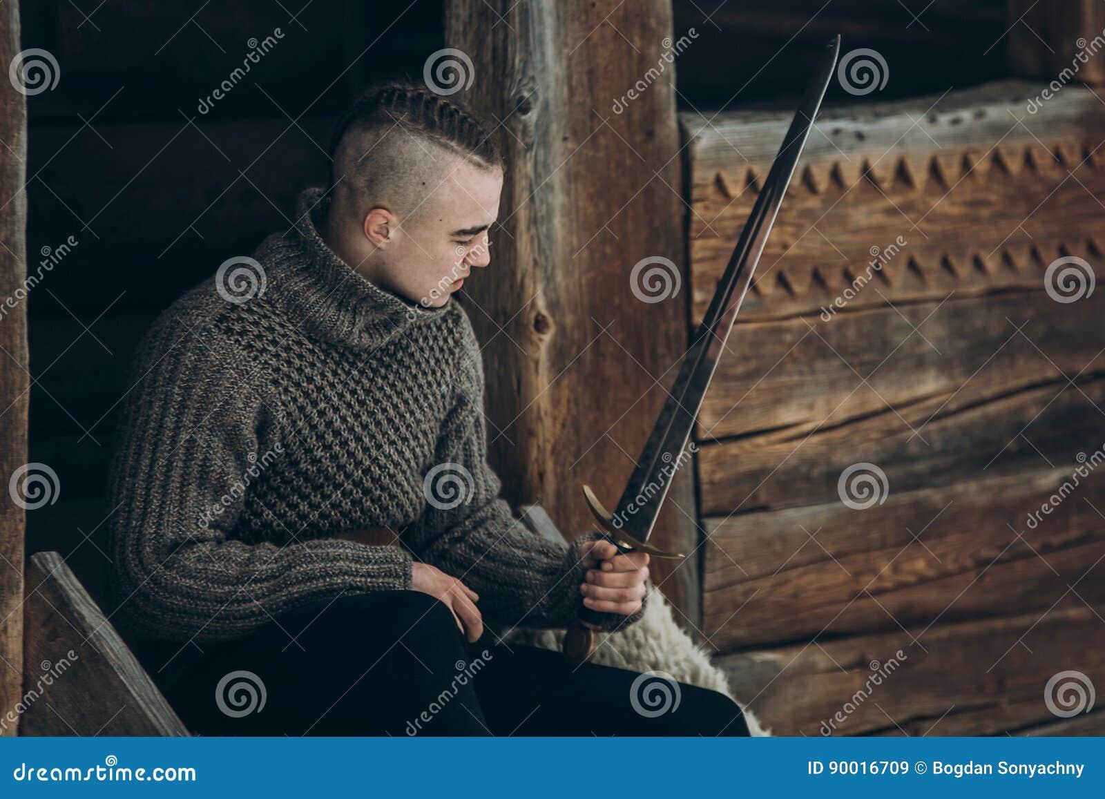 Brave warrior holding sword near historical wood castle building