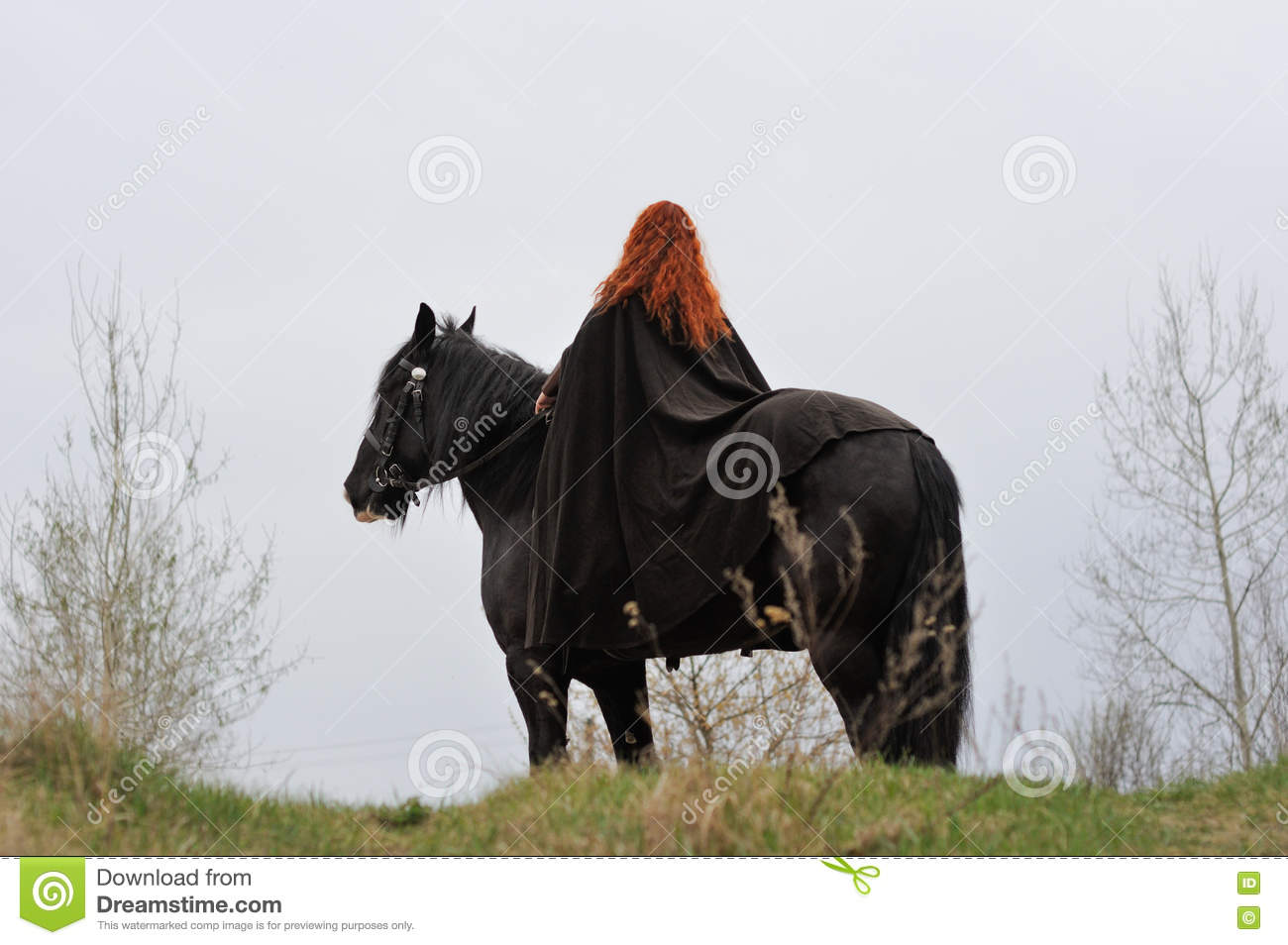 Brave woman with red hair in black cloak on friesian horse