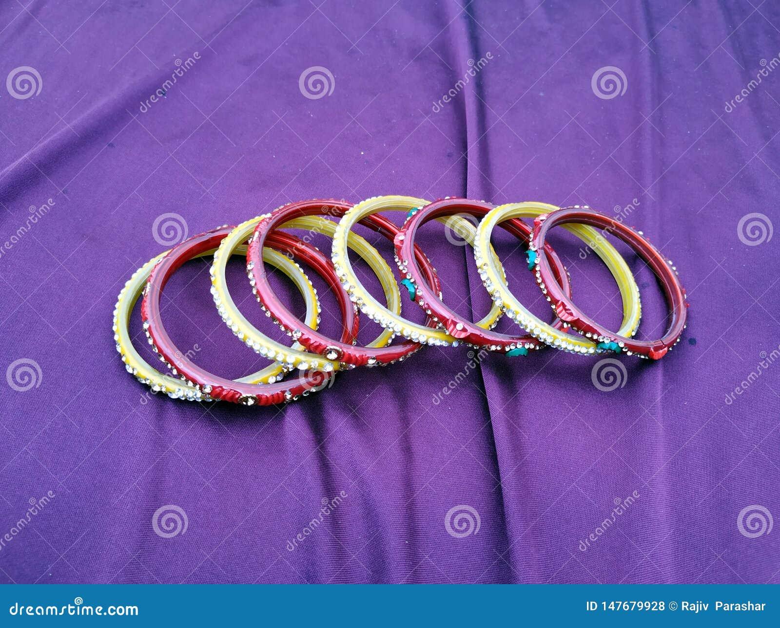 Brazaletes indios muchos brazaletes del color en el fondo violeta