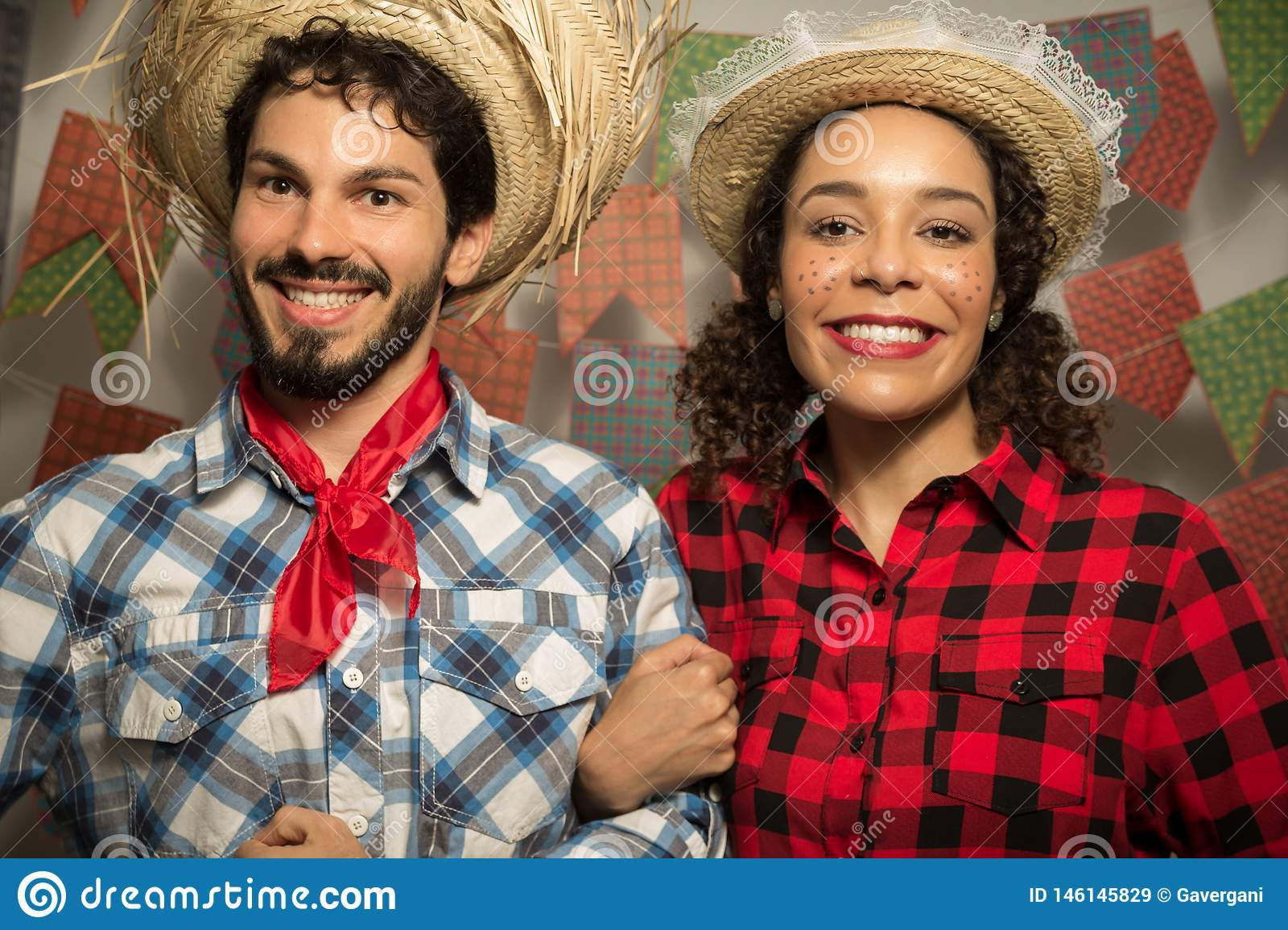 Festa Junina is June party in Brazil. Beautiful couple is holding hands and posing for the photo. They are wearing straw hats and