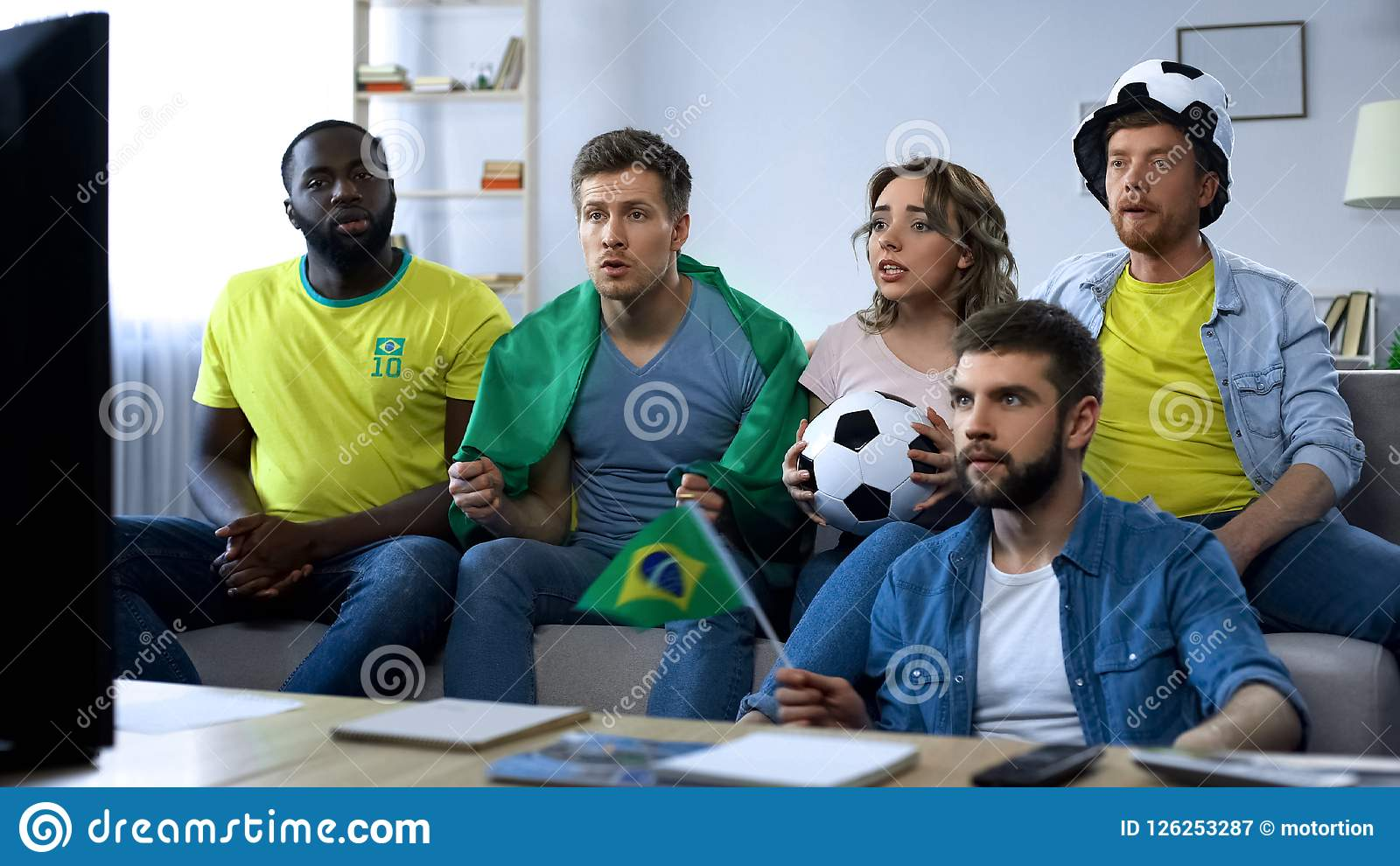 Brazilian group of friends watching football game on tv at home, togetherness