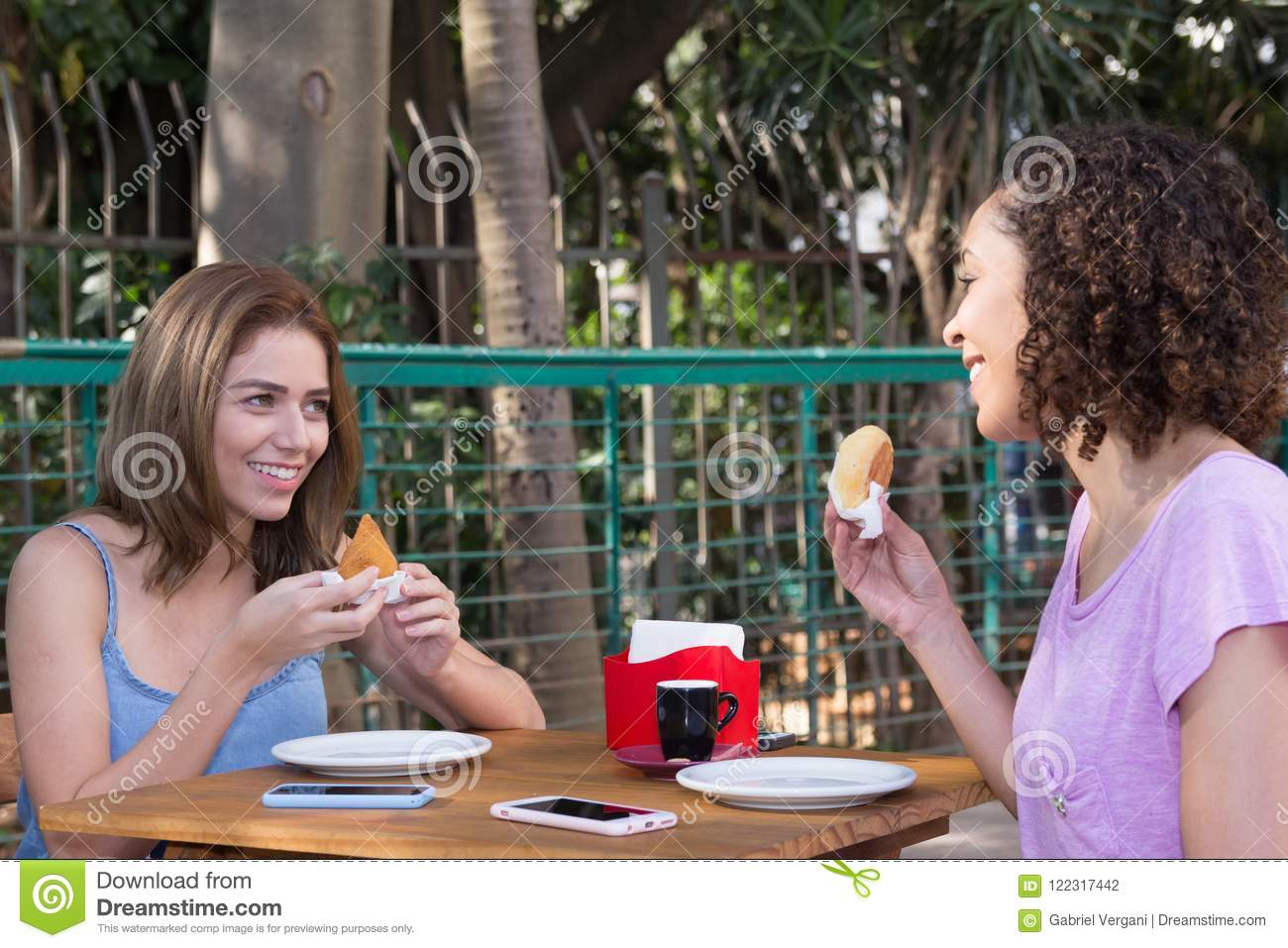 Brazilian girl friends eating pao de queijo and coxinha food snack outdoors in Sao Paulo during summer.