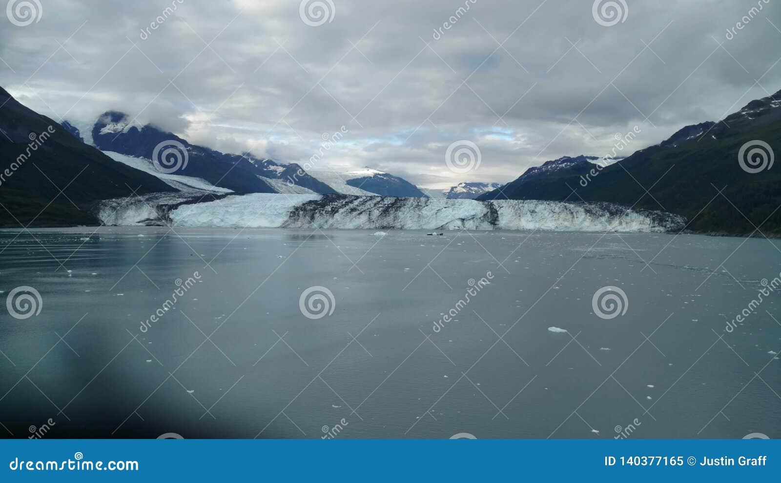 Brazo de Alaska Harvard del fiordo de la universidad del glaciar de Harvard con los picos de montaña nevados y Océano Pacífico tr
