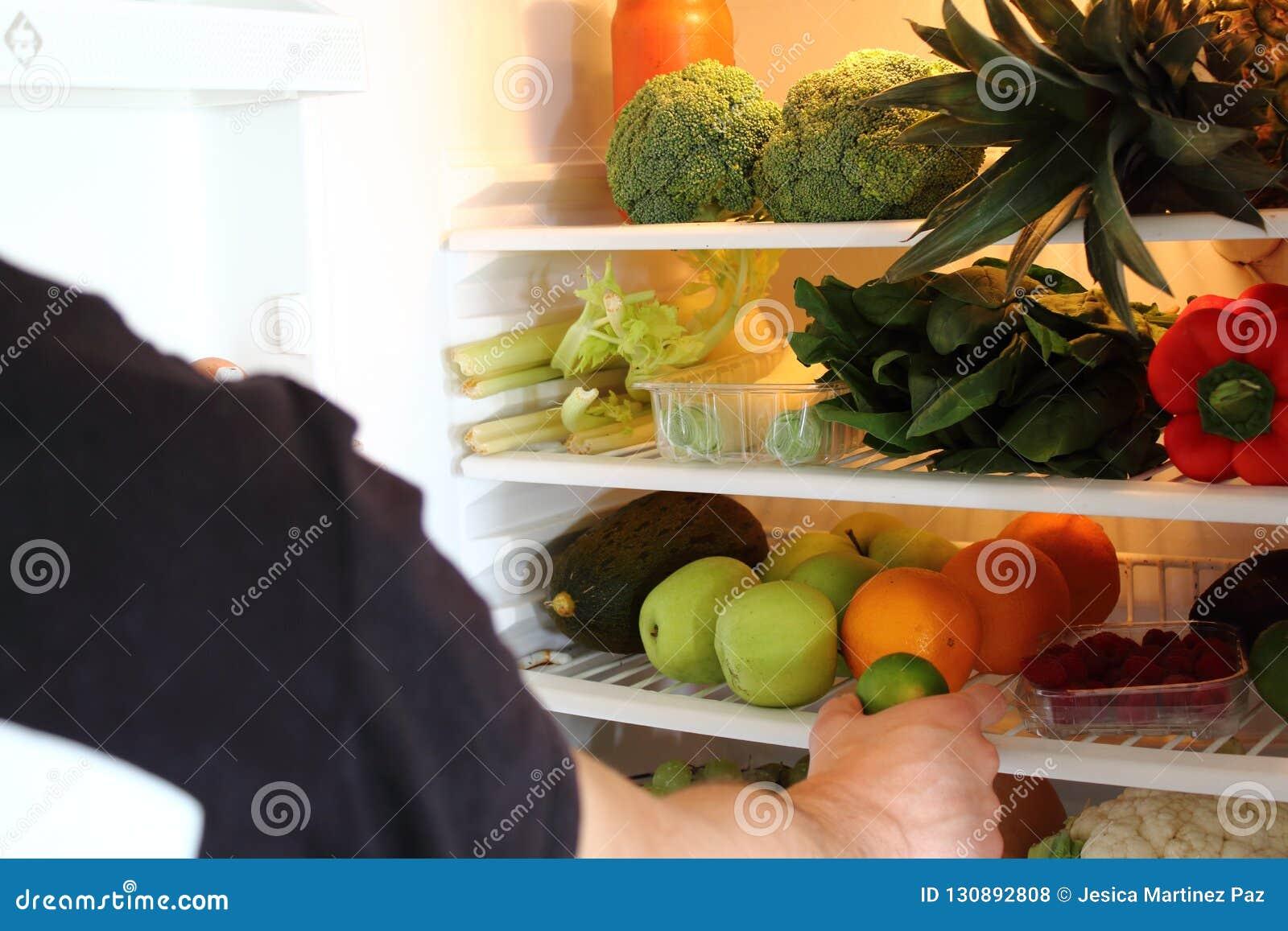 Brazo humano que alcanza para la fruta de la cal en refrigerador abierto por completo
