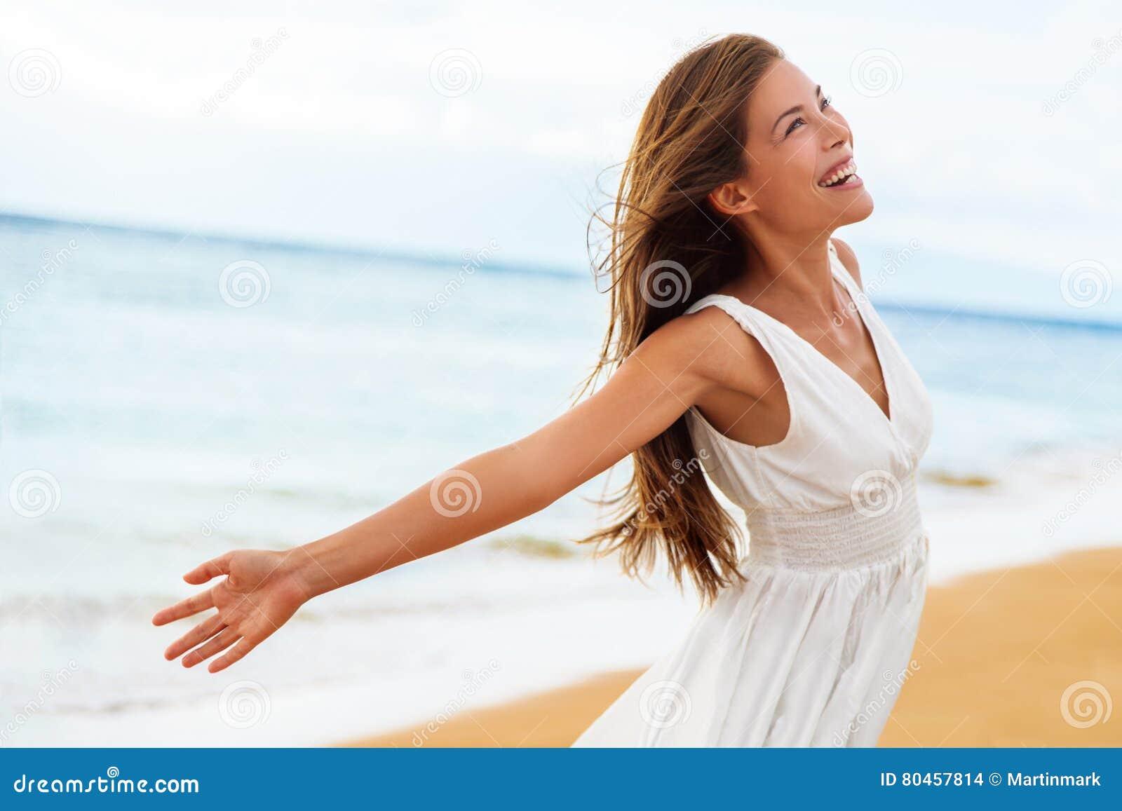 Brazos abiertos de la mujer feliz libre en la libertad en la playa