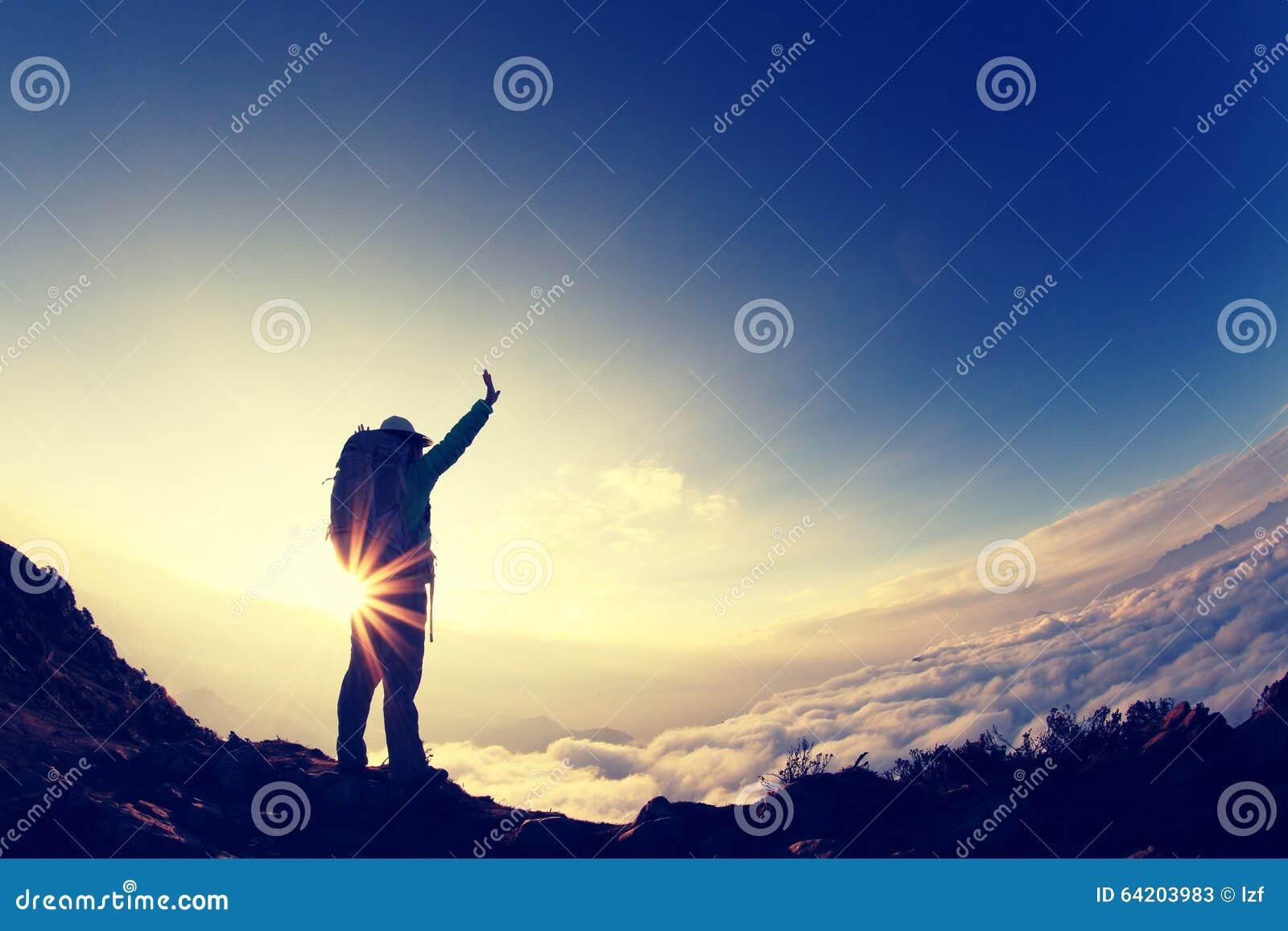 Brazos abiertos del caminante de la mujer joven en el pico de montaña