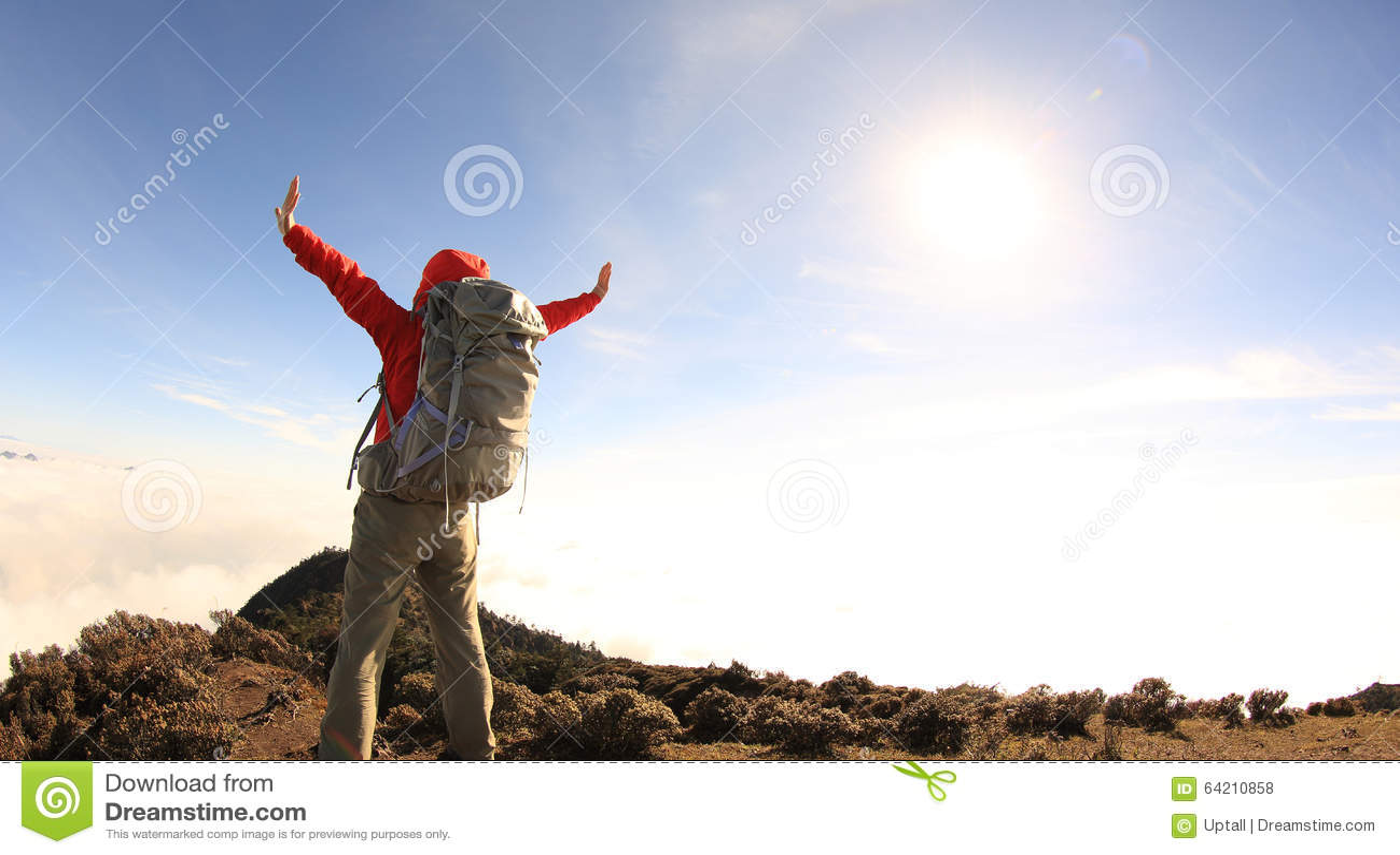 Brazos abiertos del caminante del backpacker de la mujer en el pico de montaña hermoso