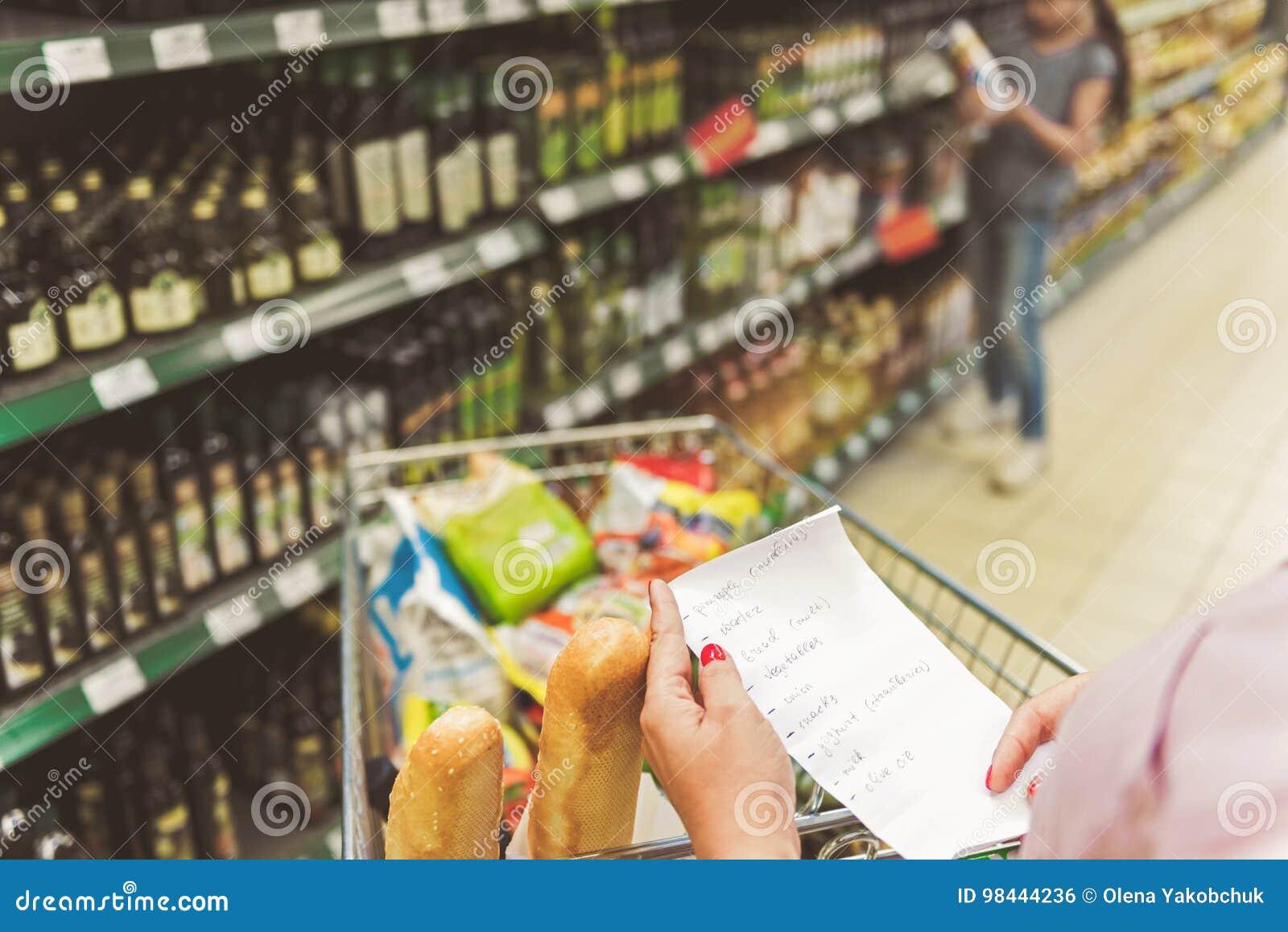 brazos de la mujer que mantienen el comprar de la lista supermercado