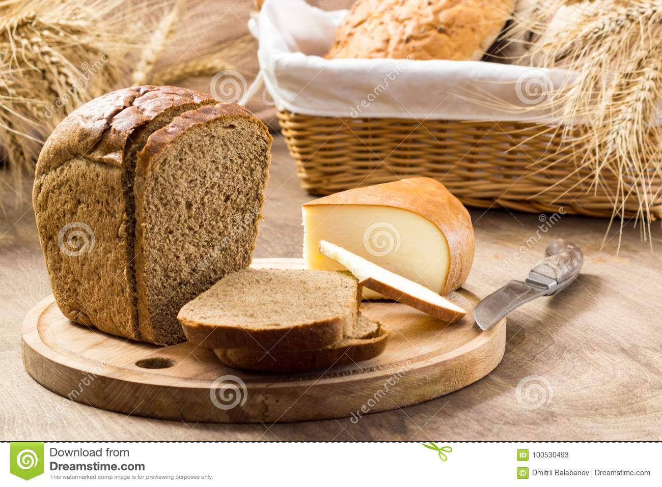 Bread and cheese sliced for sandwiches amid the loaves in a wicker basket with ears of wheat