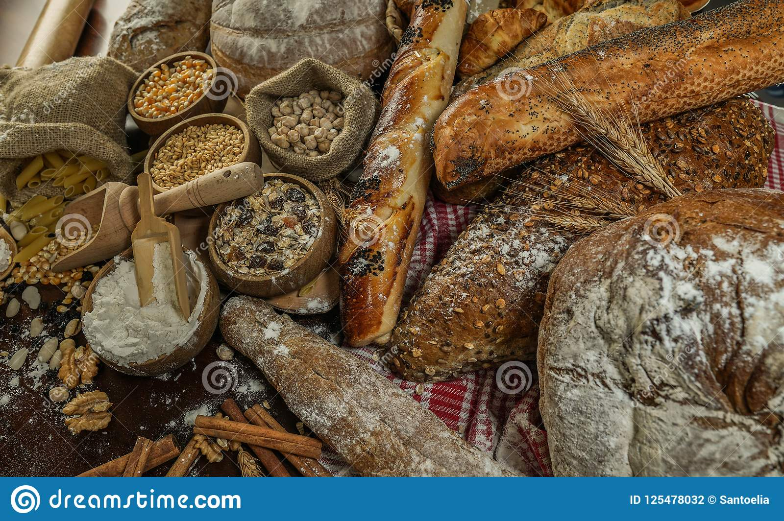 Bread background. Brown and white whole grain loaves wrapped in kraft paper composition on rustic dark wood with wheat ears scatte