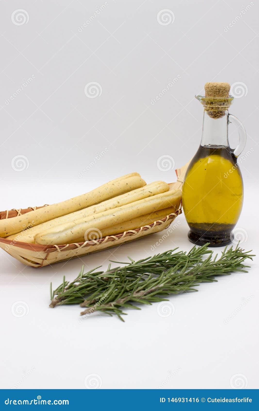 Breadsticksgrissini op rieten plaat, citroenen, en olijfolie