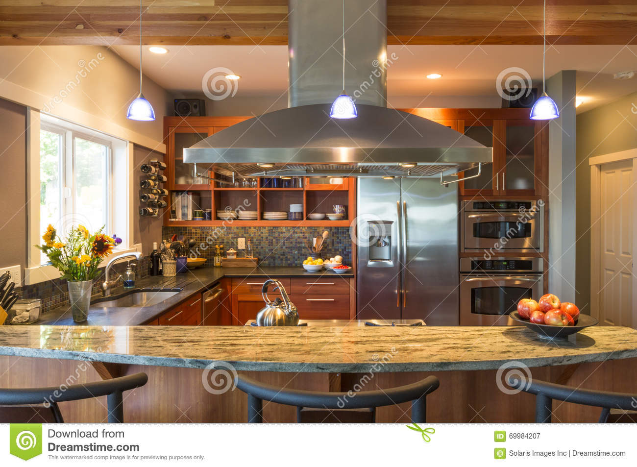 Breakfast bar in contemporary upscale home kitchen interior with granite countertops, vent hood and accent lighting