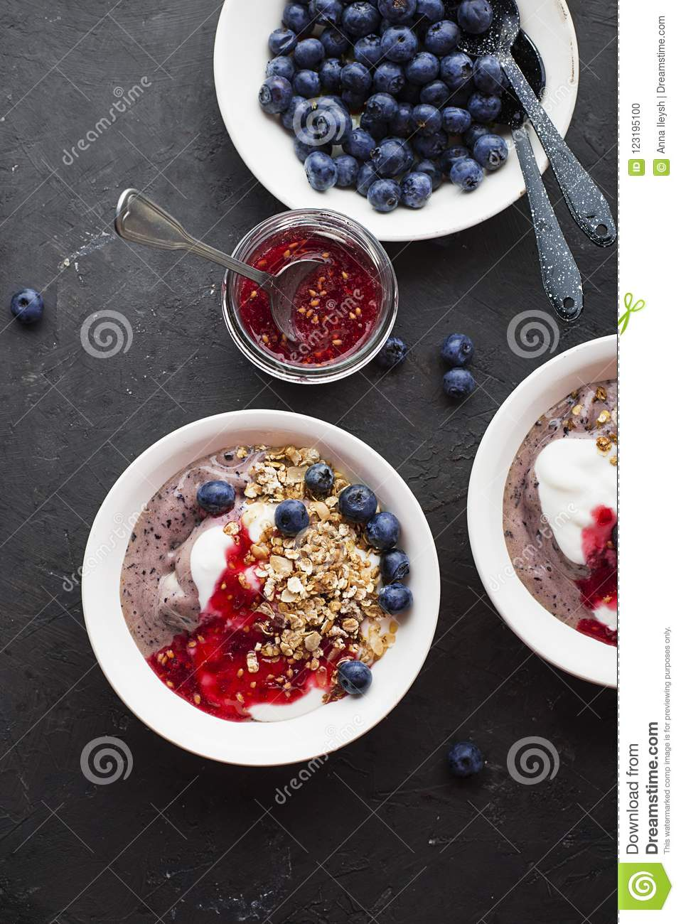 Breakfast a bowl with blueberry smoothies, pure yoghurt, homemade baked granola and fresh raw jam from red garden