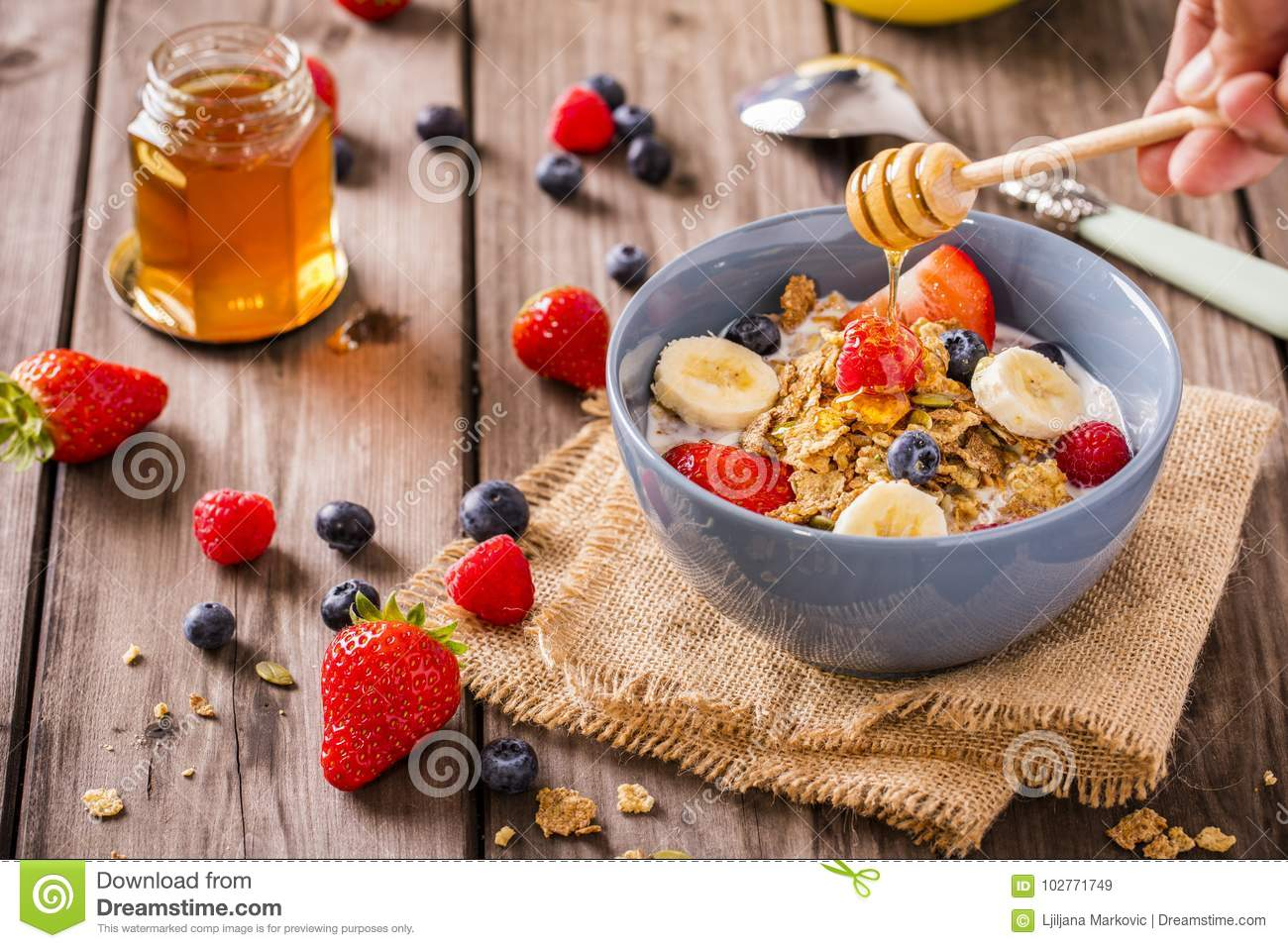 Breakfast cereal rustic with a hand swirling honey