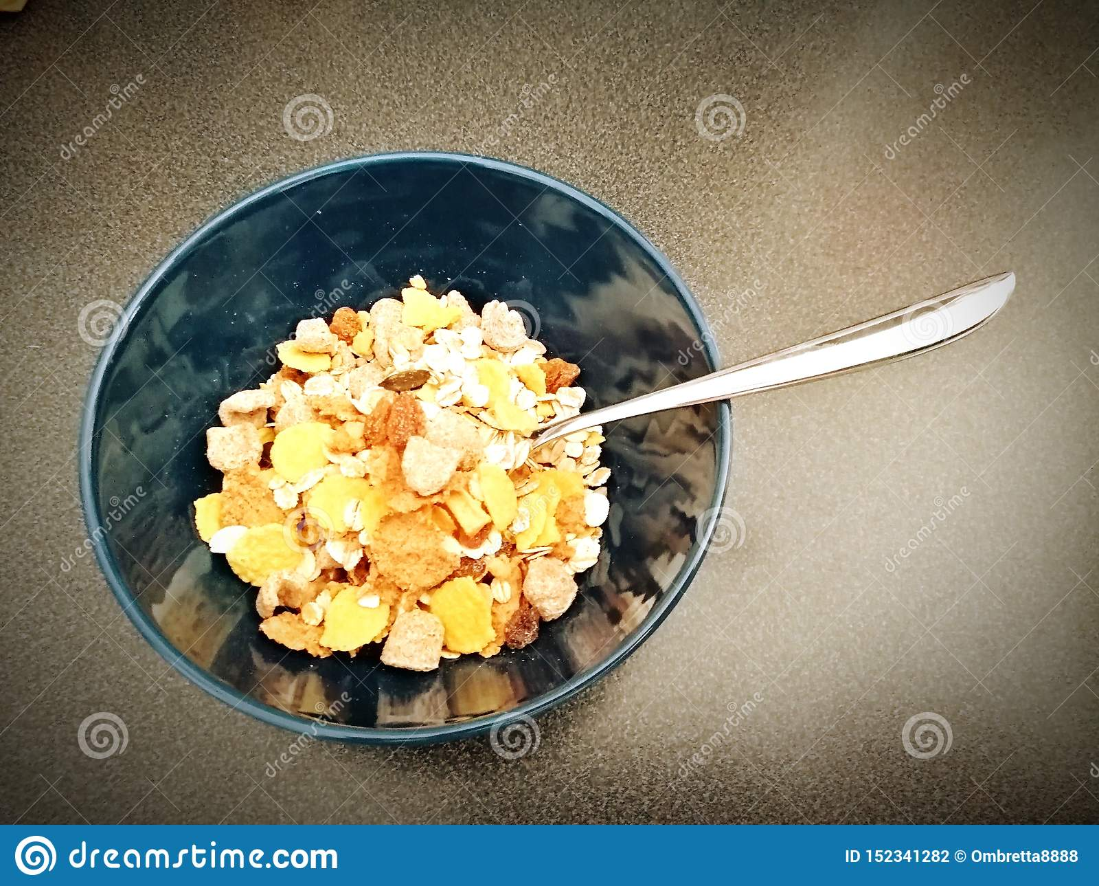 Oat flakes in a blue cup accompanied by a spoon to enjoy breakfast.