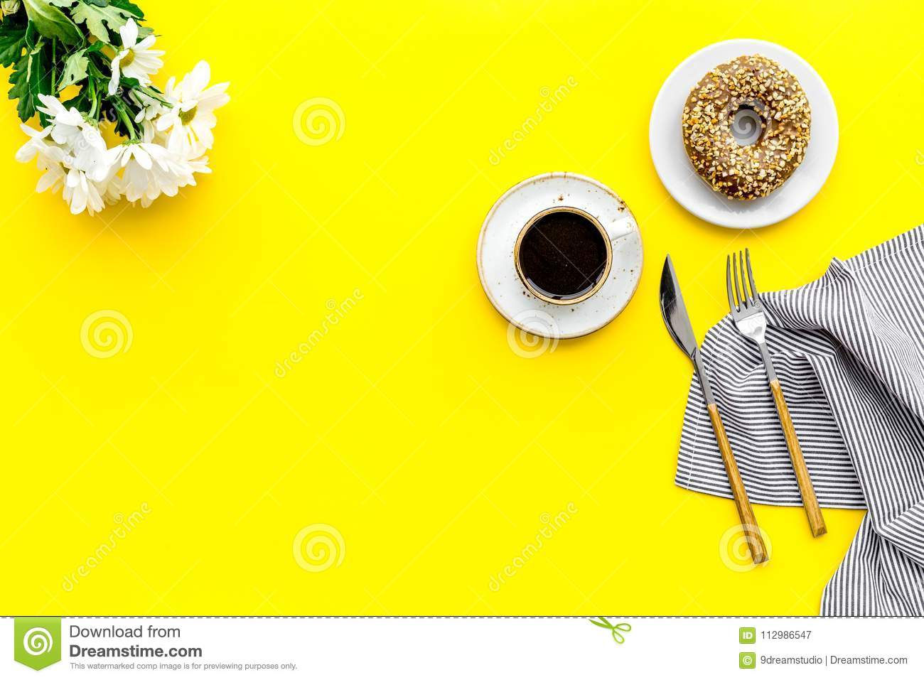 Breakfast with coffee, donuts and flowers on yellow background top view mockup