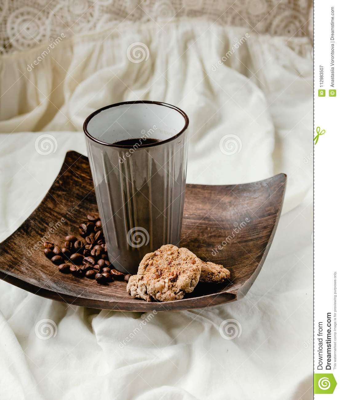 Breakfast. A cup of coffee with cookies with peanut butter, coffee beans in a wooden plate. Good morning concept.Selective focus.