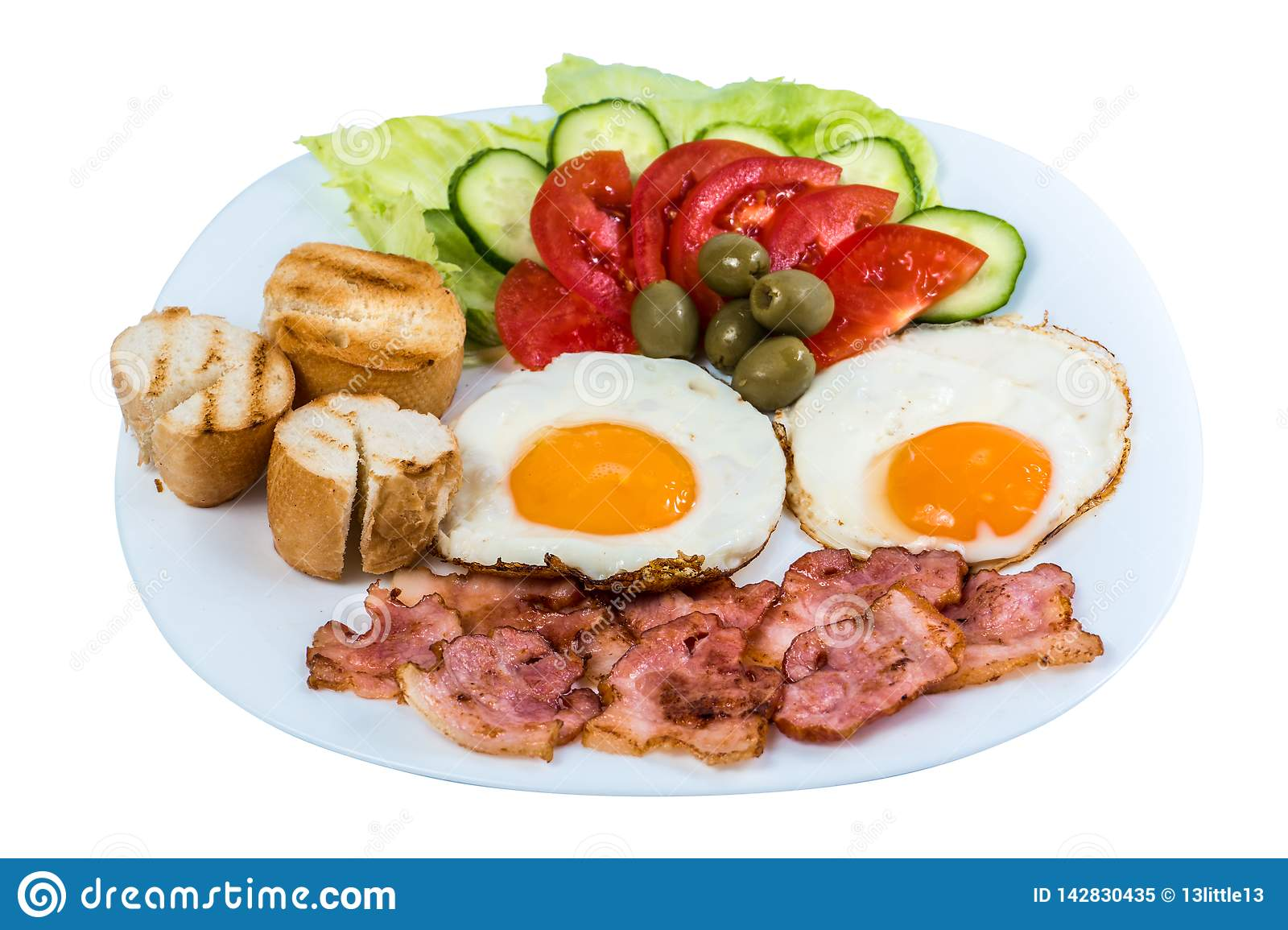 Breakfast fried egg fresh vegetables fried bacon and olives on a white plate