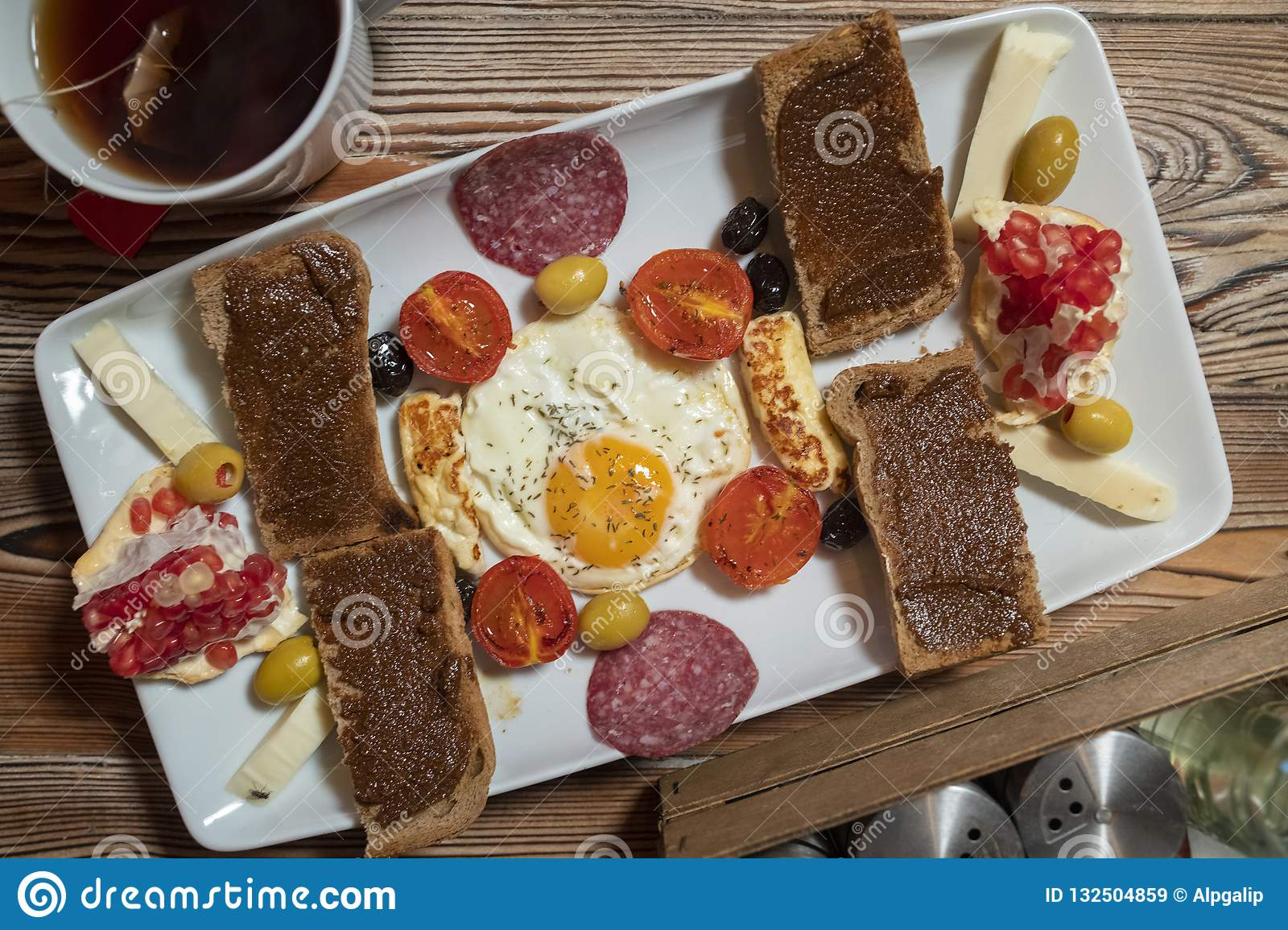 Breakfast with fried egg, rye bread, pomegranate, carob paste, cheeses, olives, dry salami, tomatoes and tea
