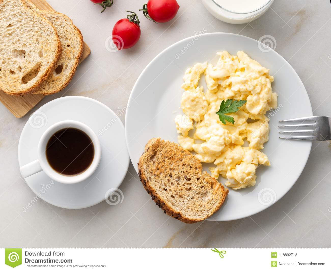 Breakfast with pan-fried scrambled eggs, cup of coffee, tomatoes on white stone background. Omelette, top view