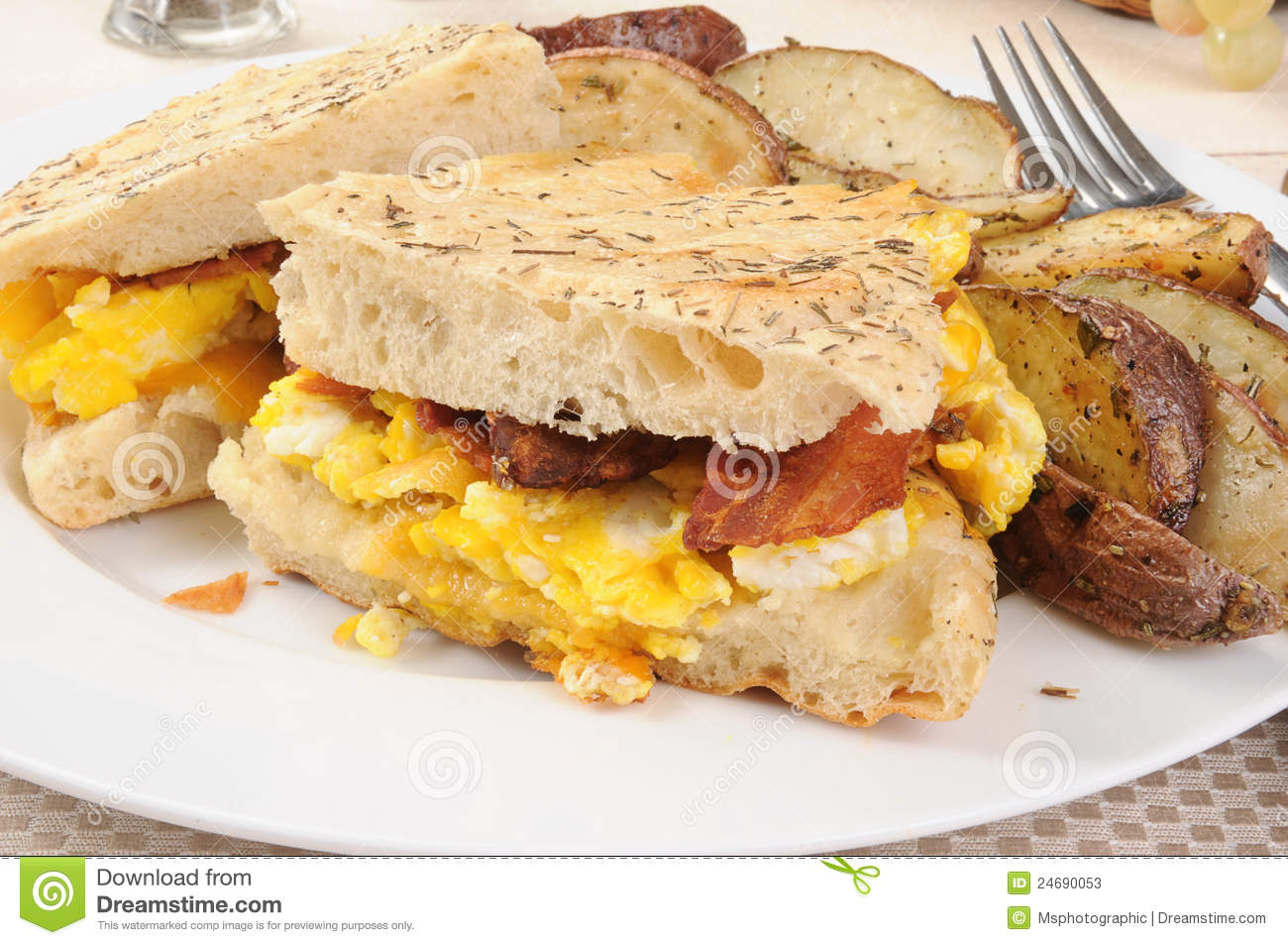 breakfast panini of bacon, eggs, cheddar cheese on a focaccia bread.
