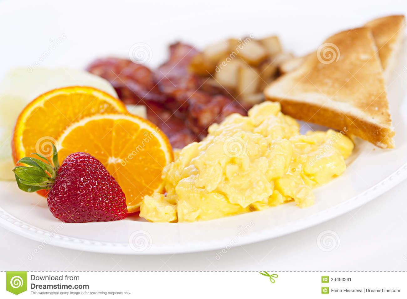 Delicious breakfast of scrambled eggs toast and bacon.