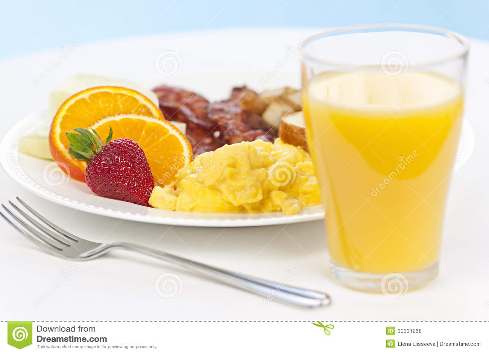 Healthy breakfast of scrambled eggs bacon fruit and orange juice.