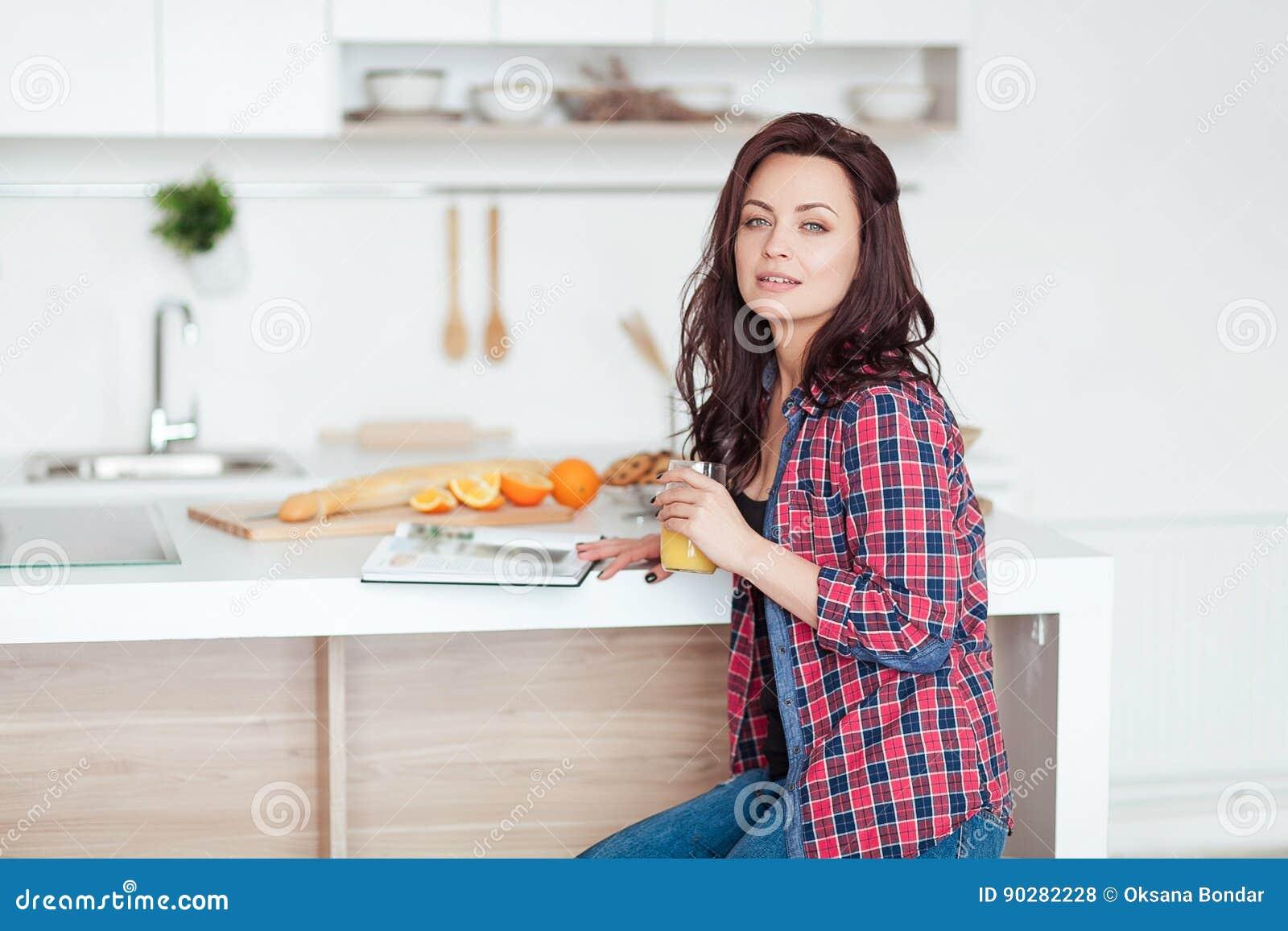 breakfast - smiling woman reading book in white kitchen, fresh