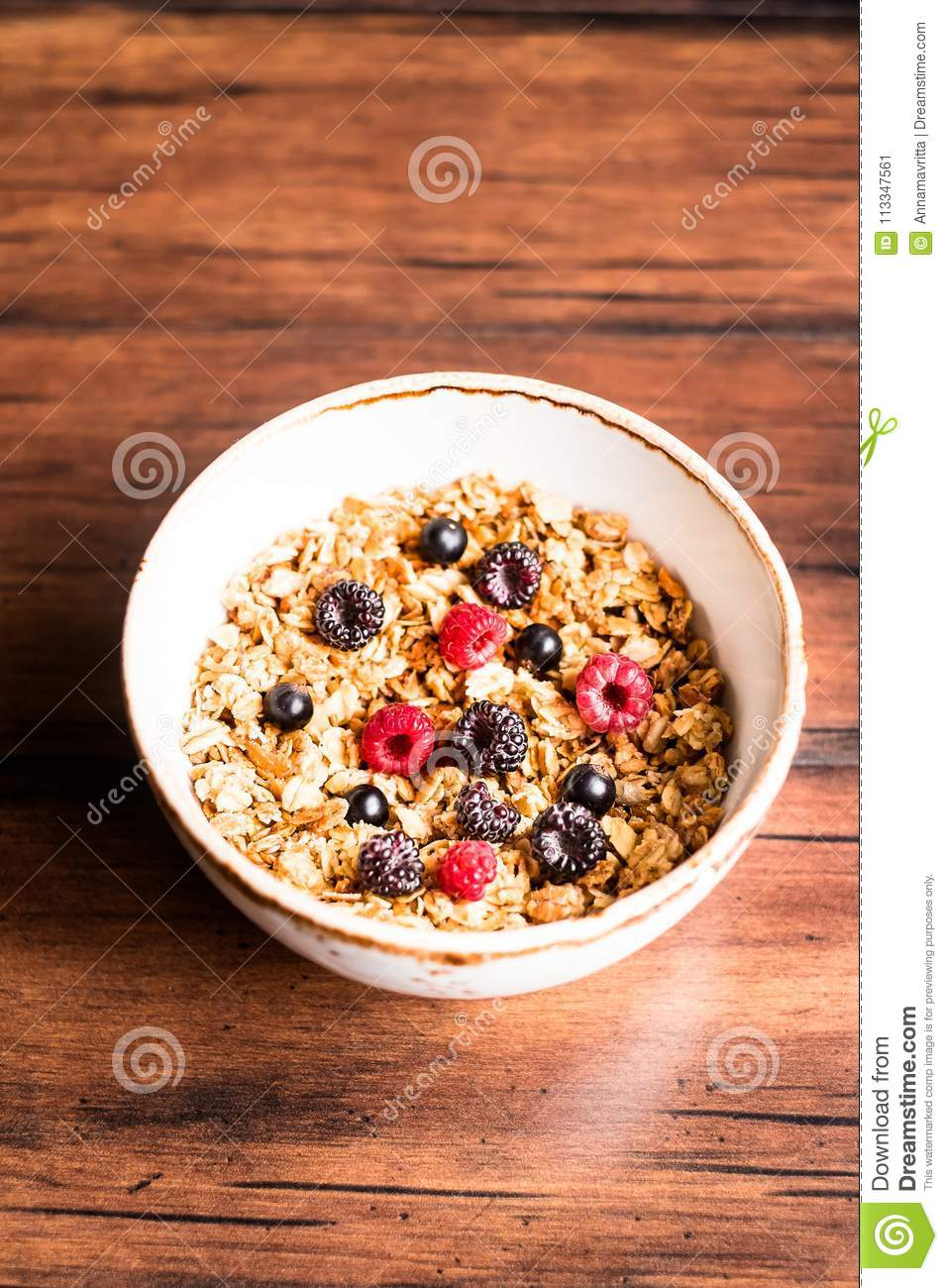 Breakfast super bowl of homemade granola or muesli with oat flakes, black currant, black raspberry and peanuts on a wooden table,