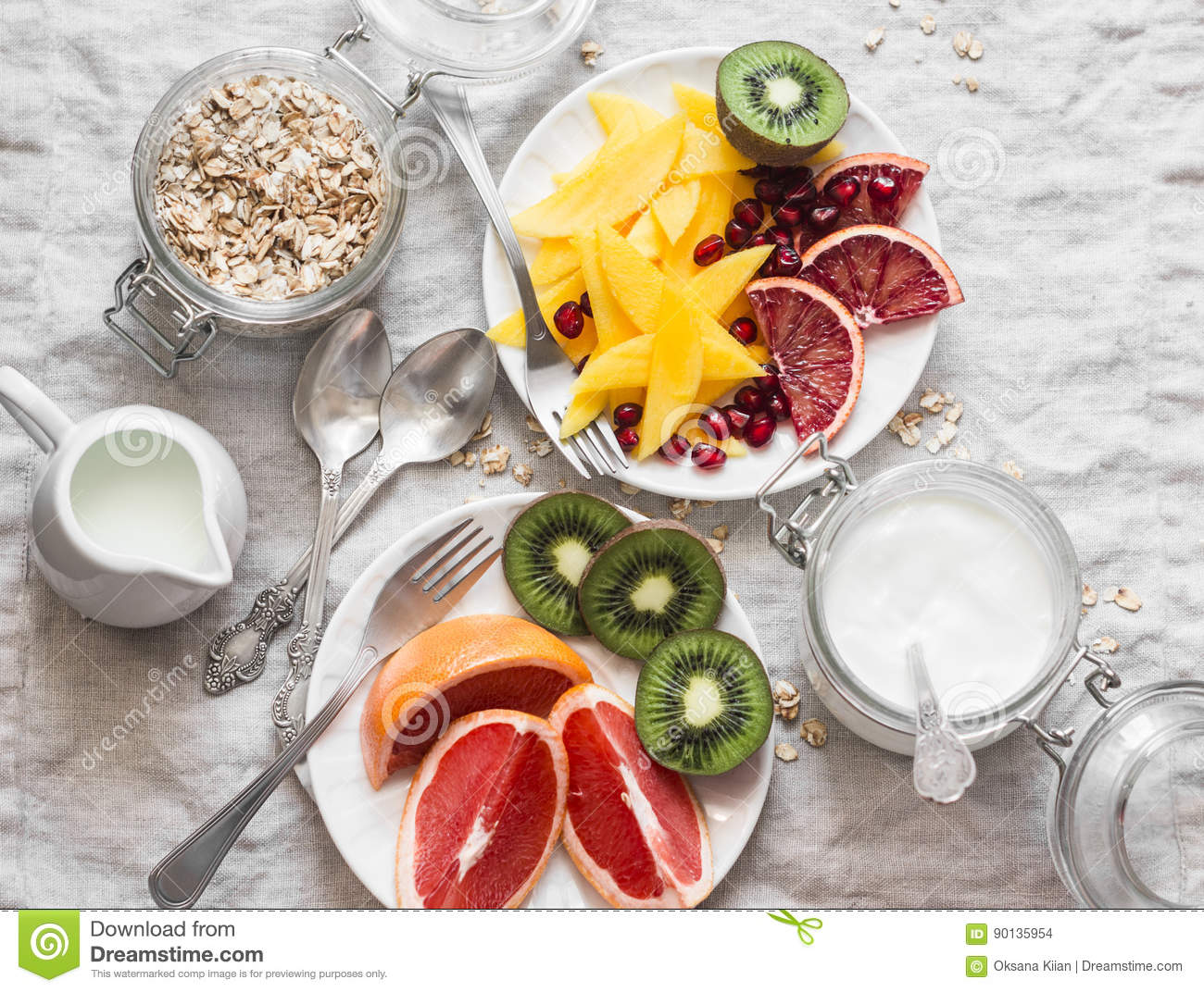 Breakfast table. Variety of fruits - mango, kiwi, grapefruit, orange and greek yogurt, oat flakes on a light background, top view.
