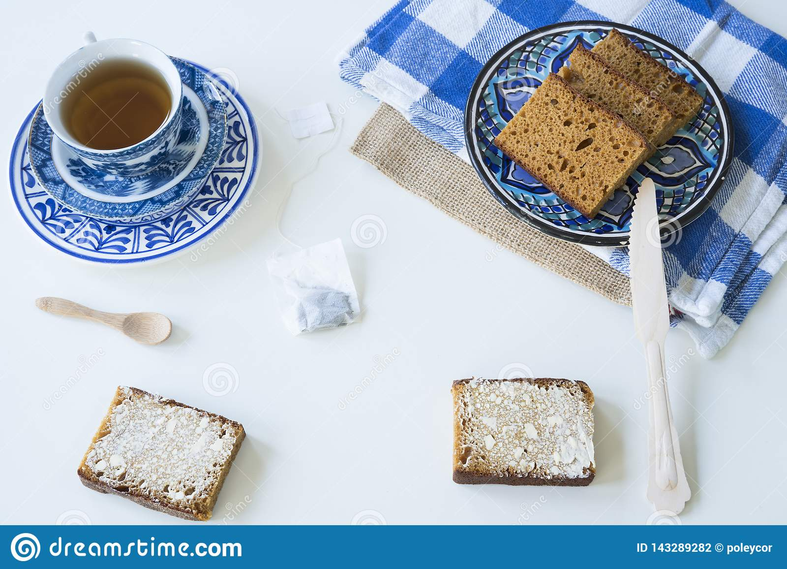 Breakfast with traditional Dutch spiced caked called ontbijtkoek or peperkoek. cup of tea, white background