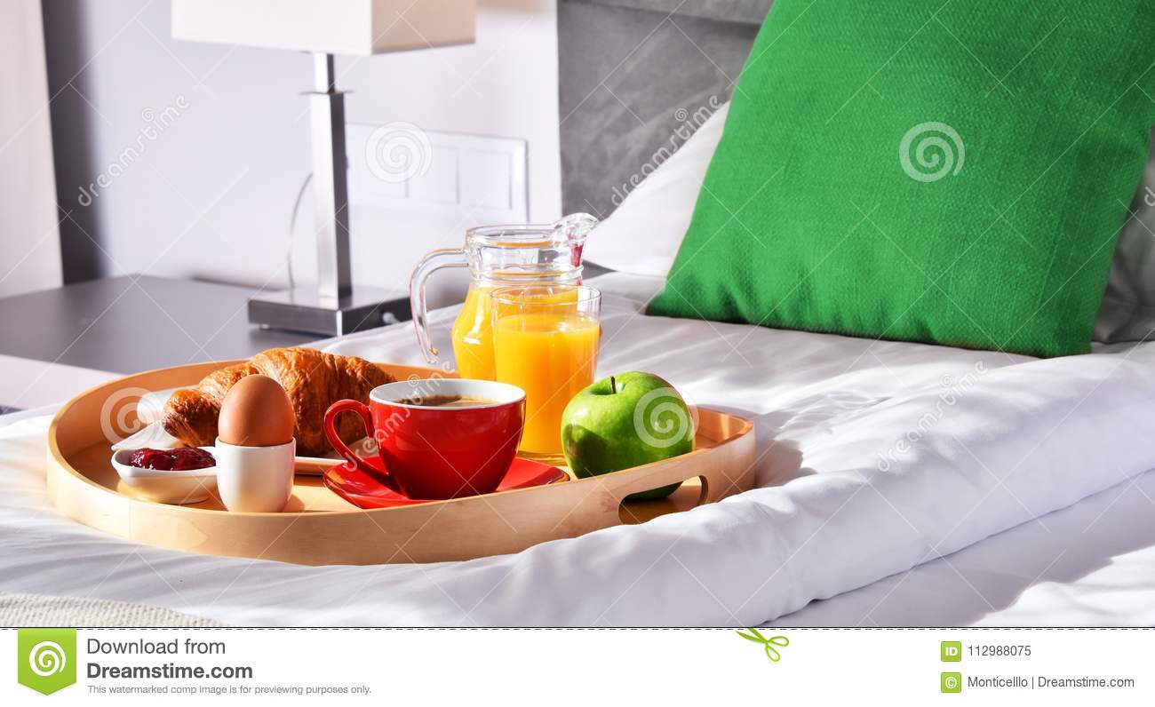 Breakfast on tray in bed in hotel room