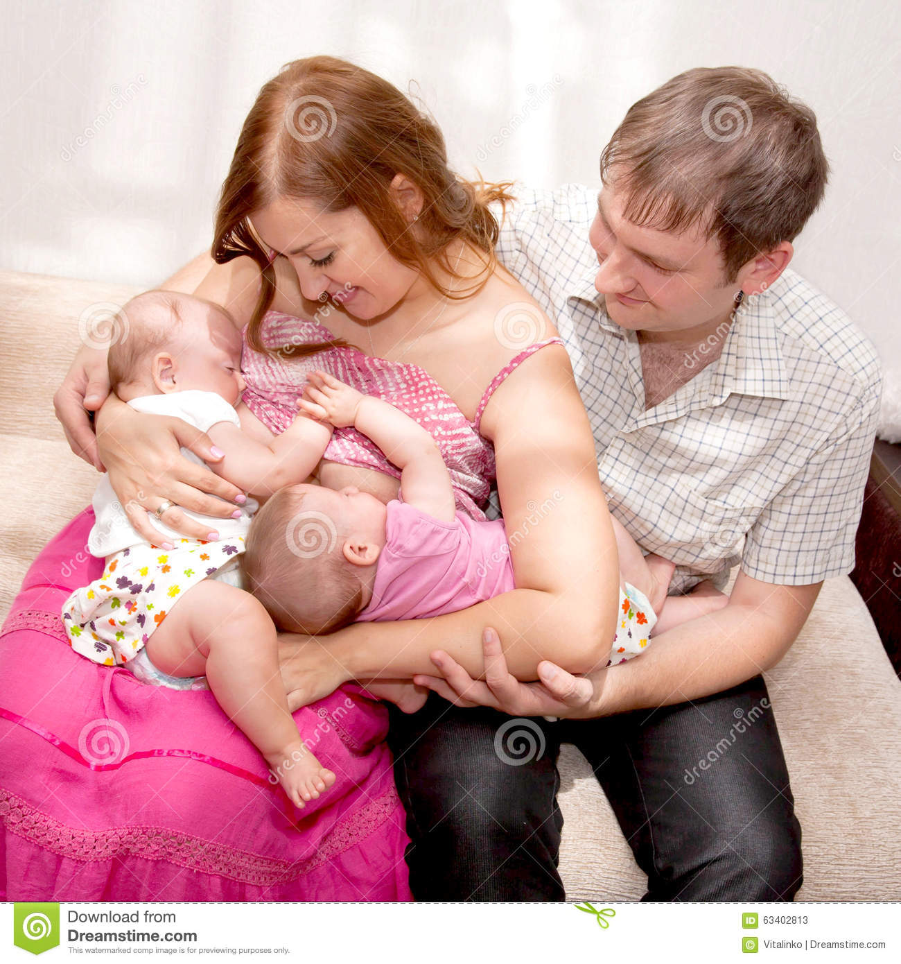 breast-feeding twin babies at home. stock image - image of concept
