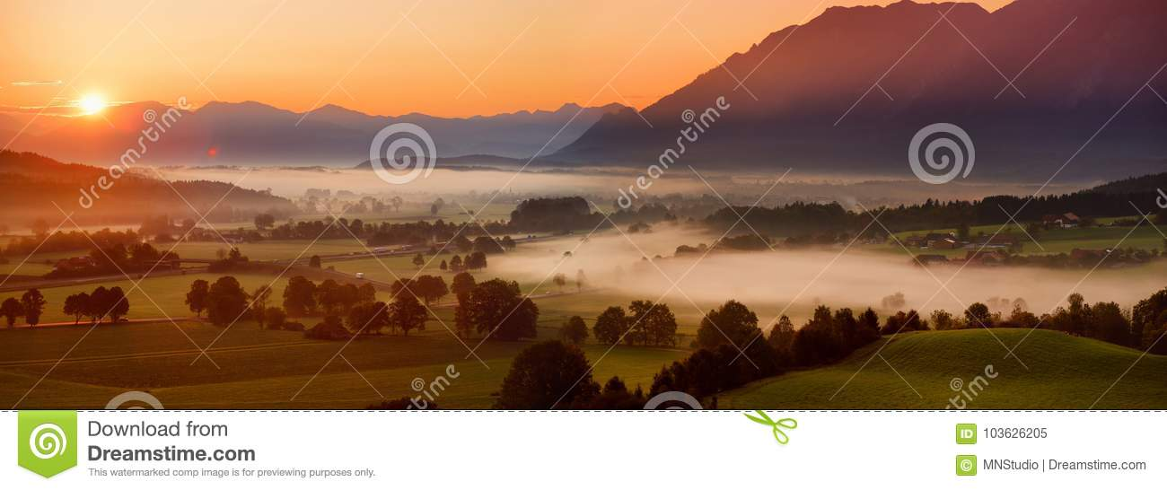 Breathtaking morning lansdcape of small bavarian village covered in fog. Scenic view of Bavarian Alps at sunrise with majestic mou