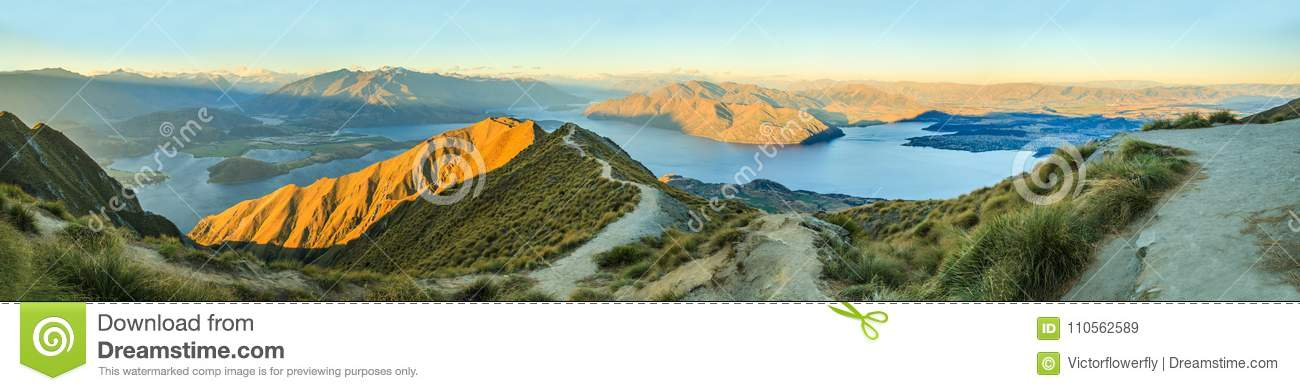 Breathtaking, Stunning Panoramic Landscape View from Roys Peak on Lake Wanaka with golden sunshine light at twilight, South Island