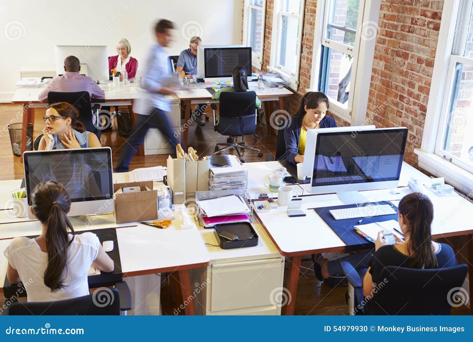 Bred vinkelsikt av det upptagna designkontoret med arbetare på skrivbord