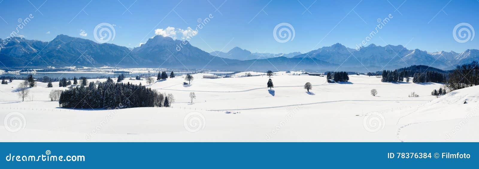 Breite Panoramalandschaft im Bayern mit Alpenbergen und im See im Winter