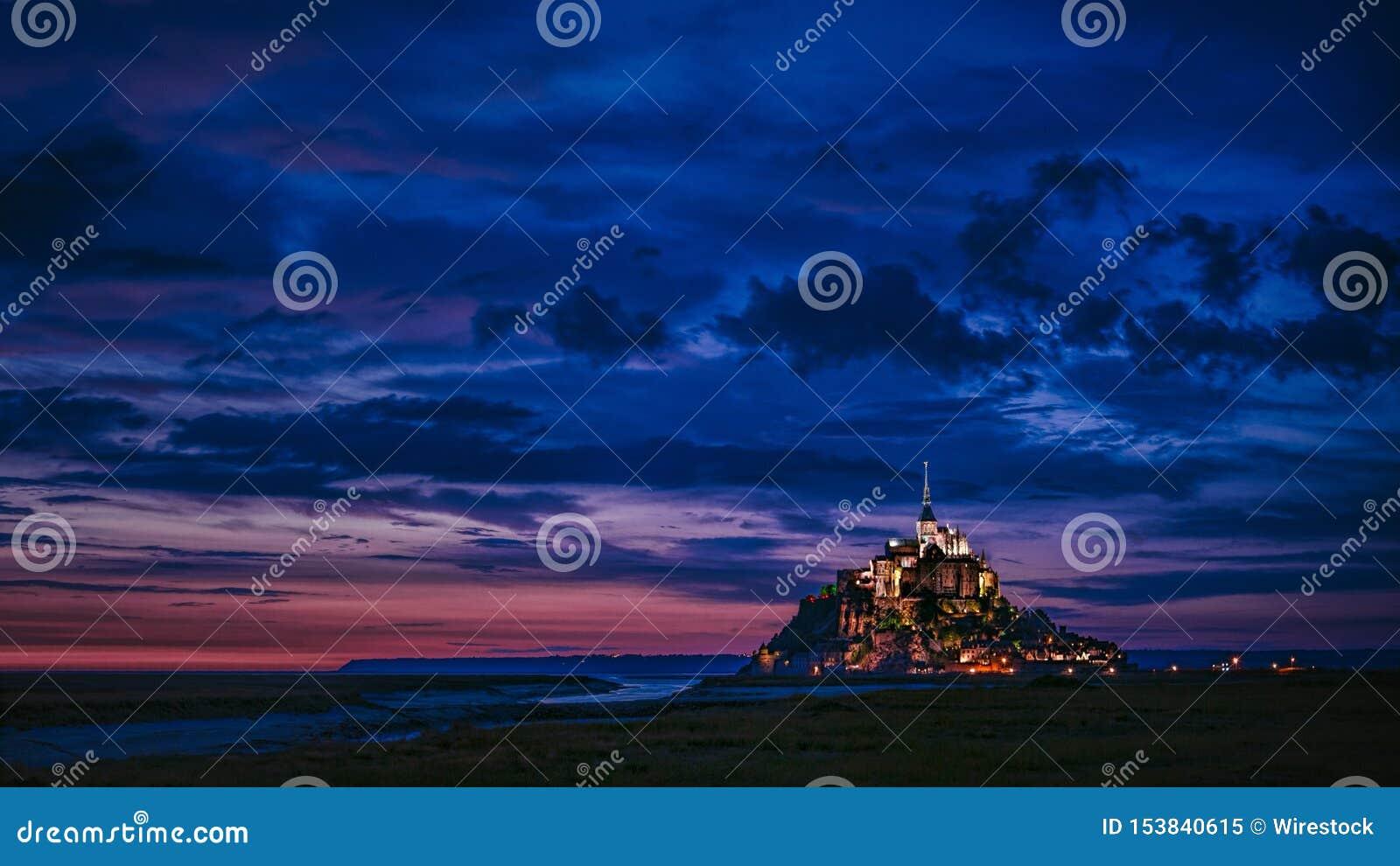 Breiter Schuss eines belichteten Schlosses im Abstand mit dem Überraschen von blauen Wolken im Himmel