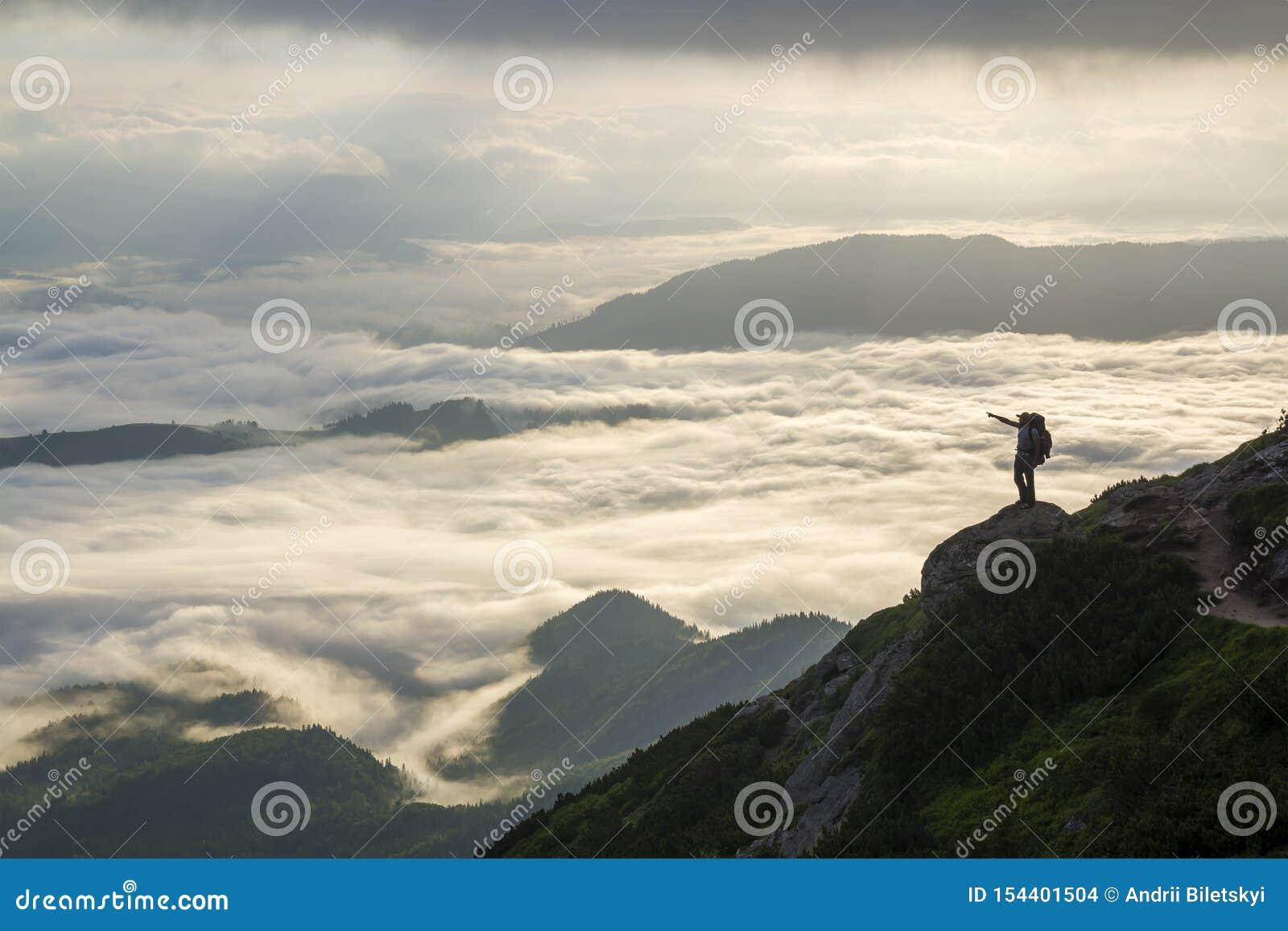 Breites Bergpanorama Kleines Schattenbild des Touristen mit Rucksack auf felsigem Berghang mit angehoben ?berreicht das bedeckte