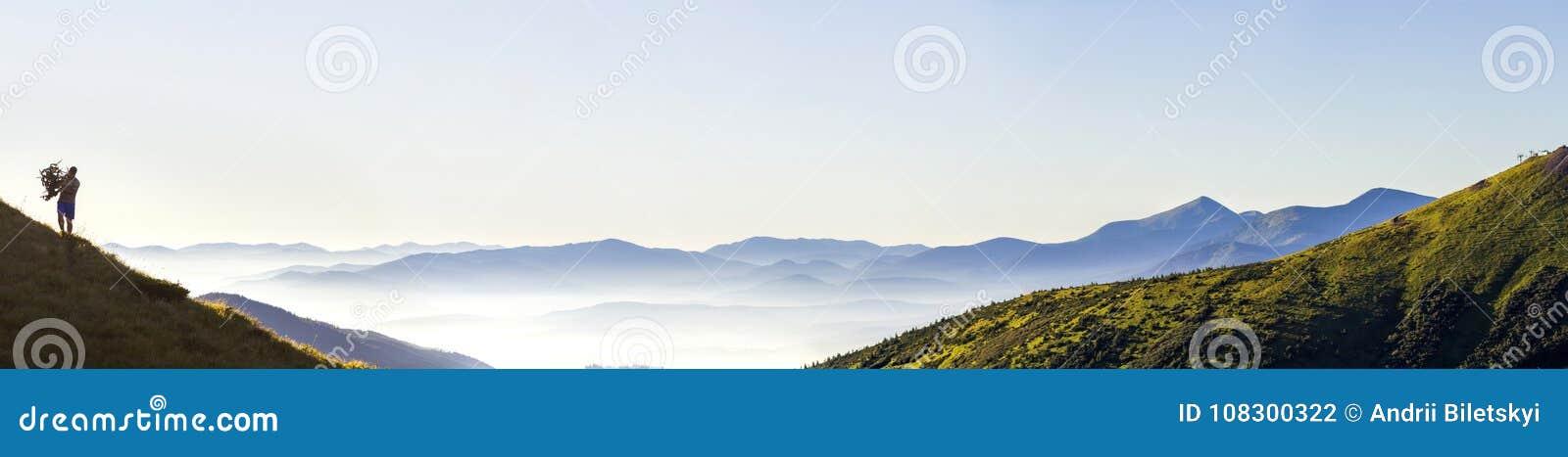 Breites Panorama von Morgengebirgshügeln und von einsamem Wanderertouristen