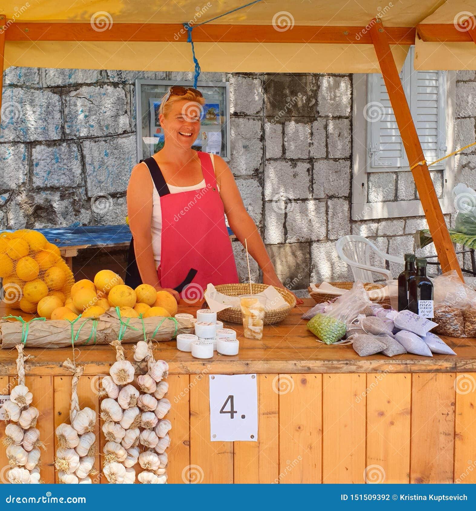 Brela Croácia - 25 de junho de 2019: Favoravelmente, a mulher de sorriso bonita está atrás do contador e vende frutas e legumes s