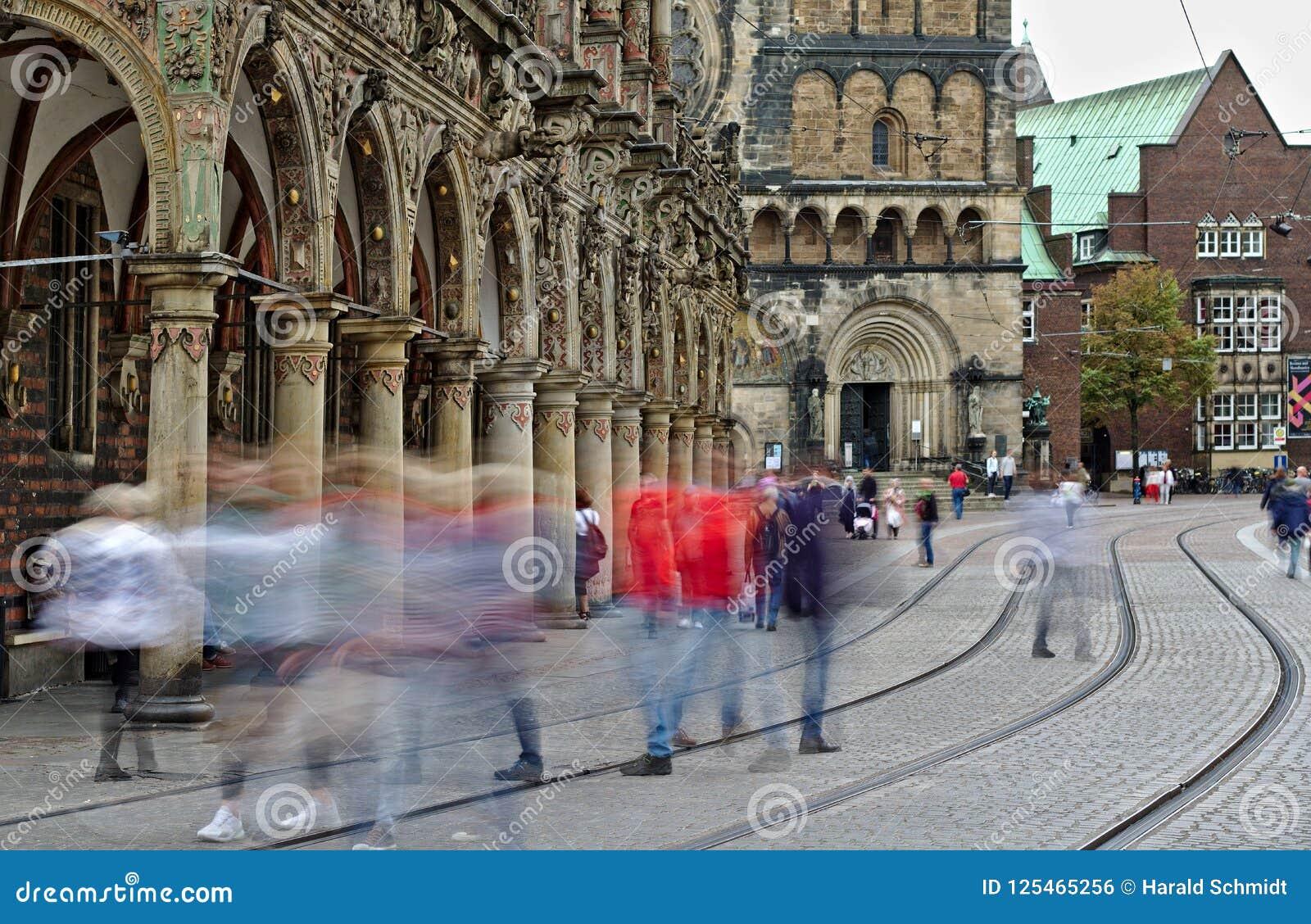 Bremen, Deutschland - unscharfe menschliche Figuren, welche lang die Straßen- und Trambahnen vor dem historischen Rathaus und der