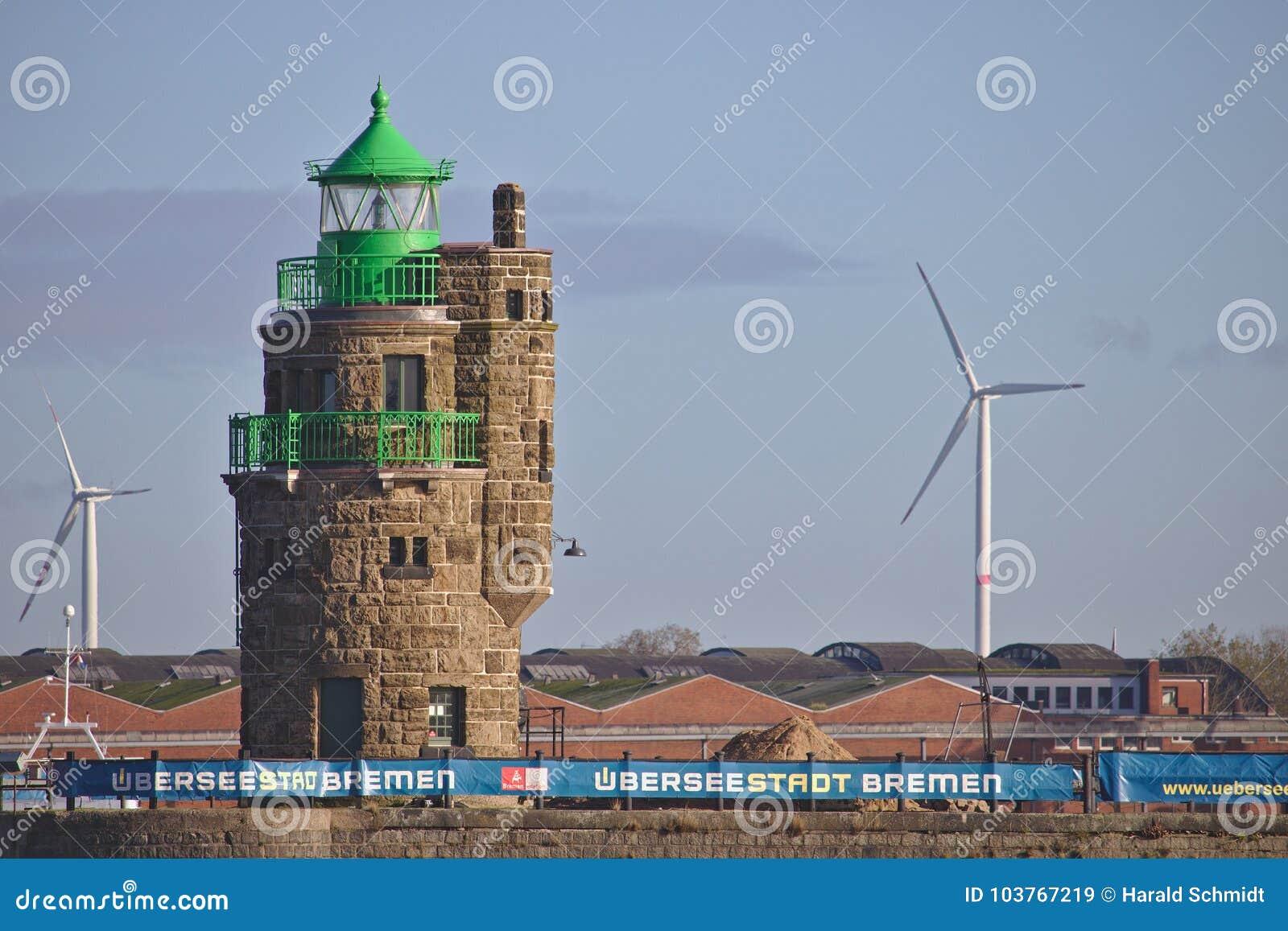 Bremen Tyskland - November 6th, 2017 - fyr på hamningången med industriella lagringsbyggnader och vindkraftstationer