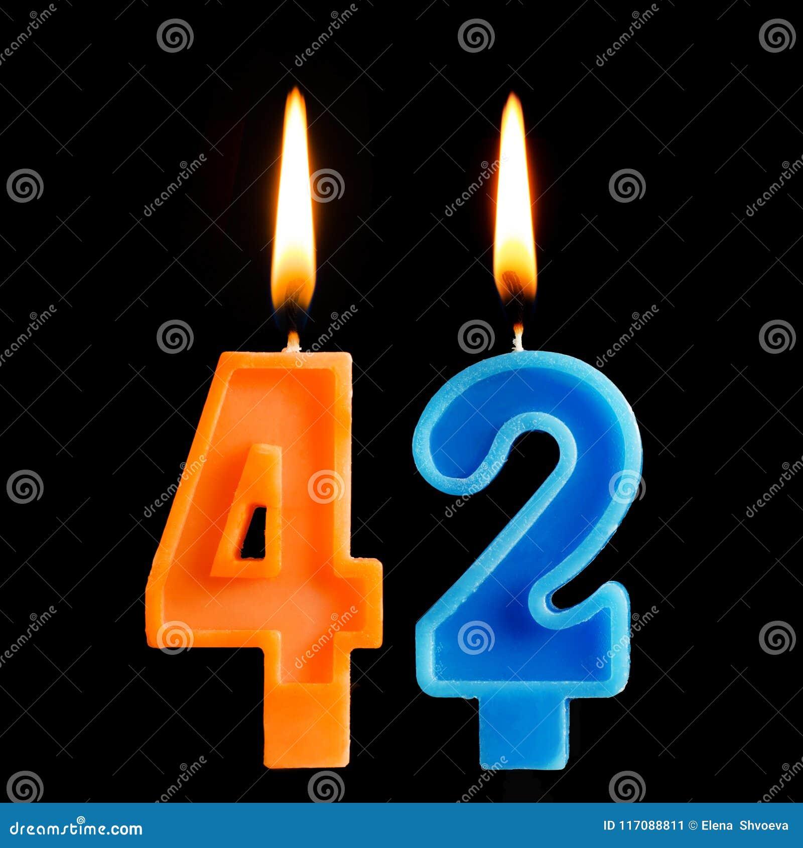 Brennende Geburtstagskerzen in Form von 42 zweiundvierzig für den Kuchen lokalisiert auf schwarzem Hintergrund