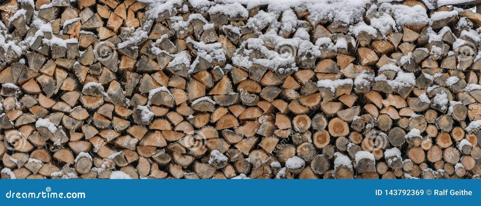 Brennholz wird im Schnee als hölzerne Beschaffenheit gespeichert