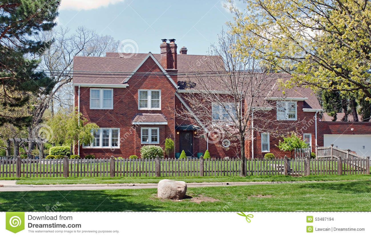 Brick Home With Natural Wood Picket Fence Stock Photo