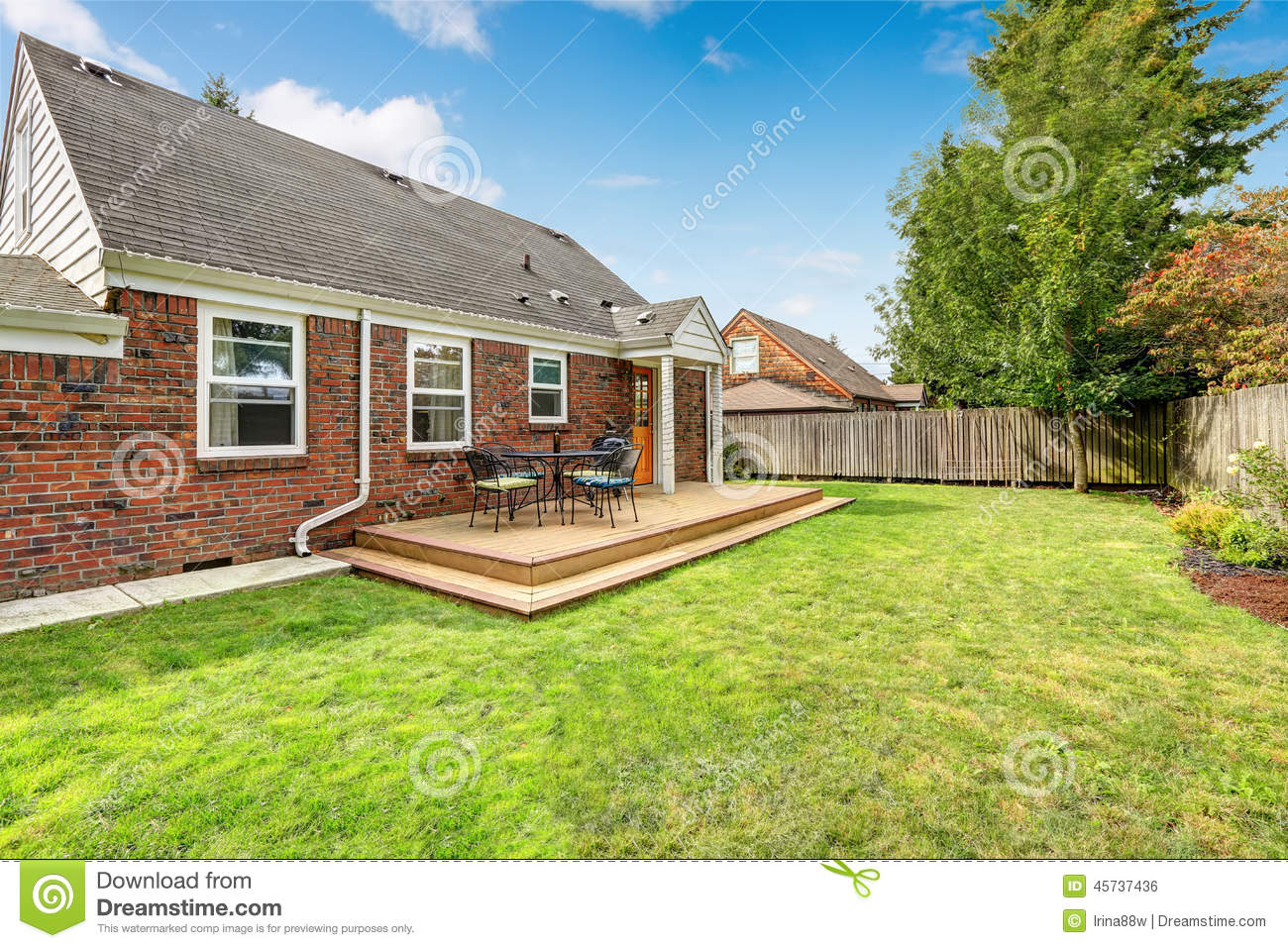 Brick House Exterior With Walkout Wooden Deck Stock Photo